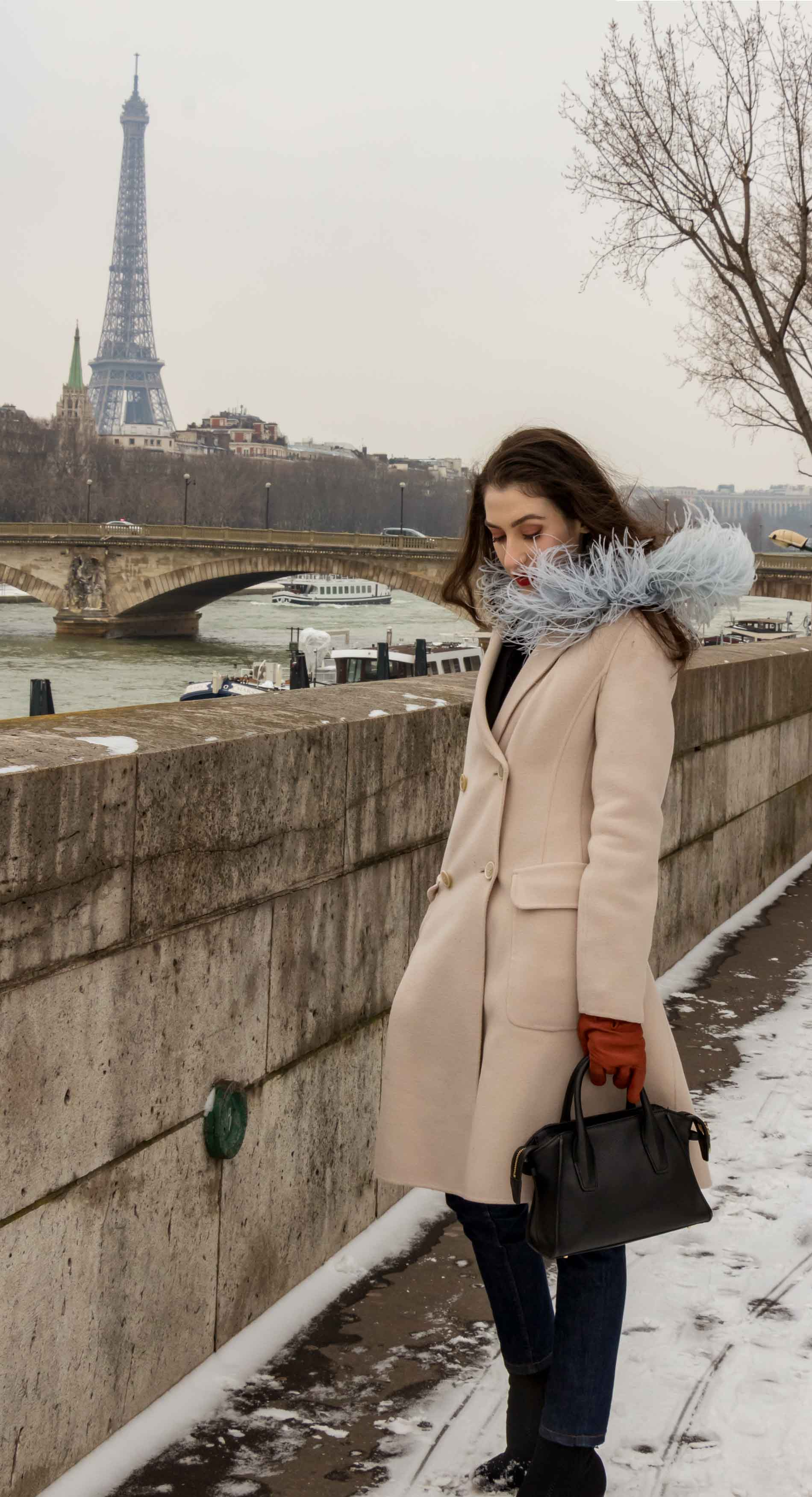 Fashion Blogger Veronika Lipar of Brunette from Wall Street dressed in feathers, Weekend Maxmara coat, dark denim jeans, black sock boots, leather gloves, standing at Pont du Alexandre III in Paris during Paris fashion week autumn winter 2018/19
