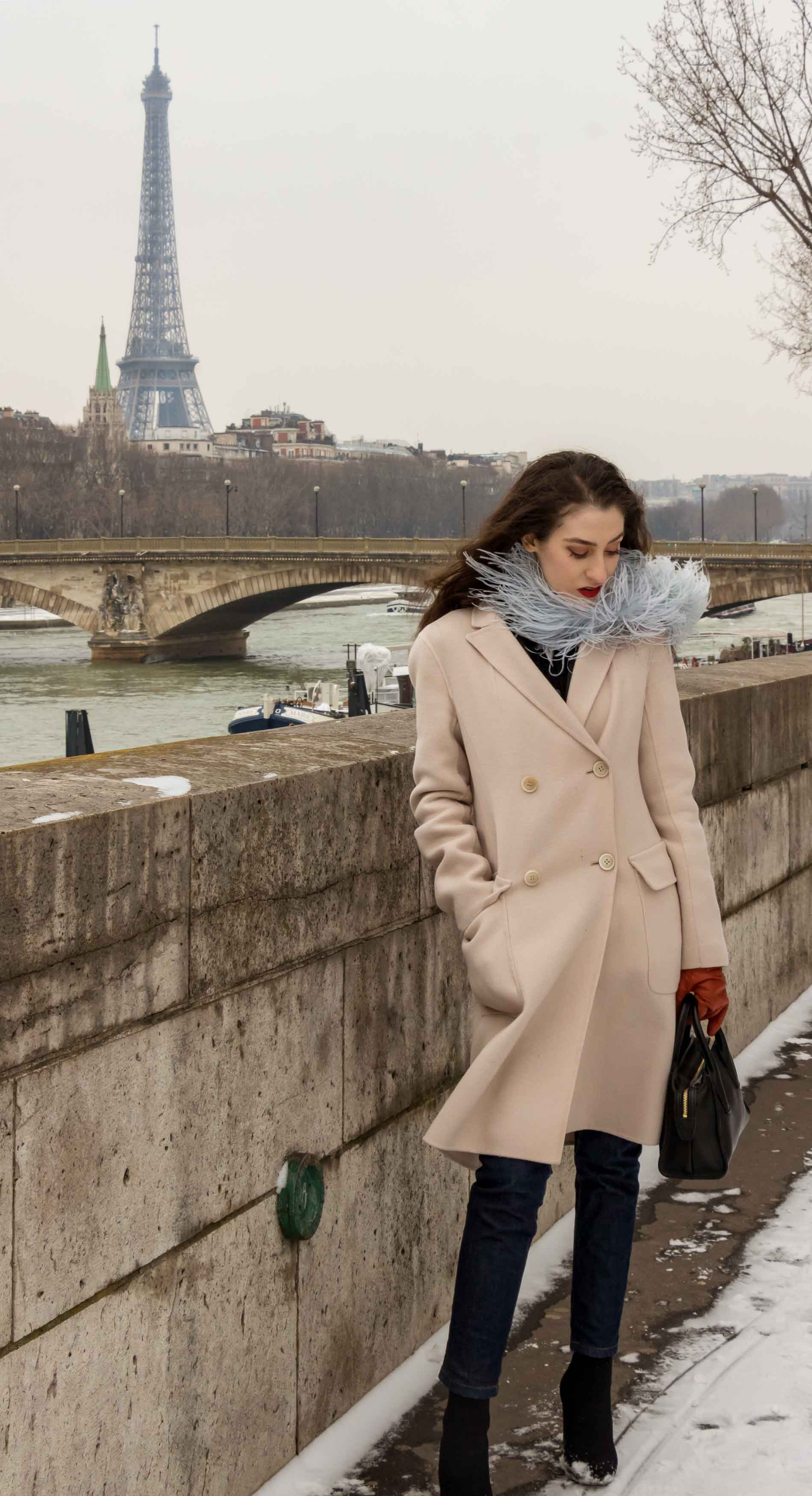 Fashion Blogger Veronika Lipar of Brunette from Wall Street wearing feathers, Weekend Maxmara coat, dark denim jeans, black sock boots, leather gloves, standing at Pont du Alexandre III with Eiffle tower in the back in Paris during Paris fashion week autumn winter 2018/19