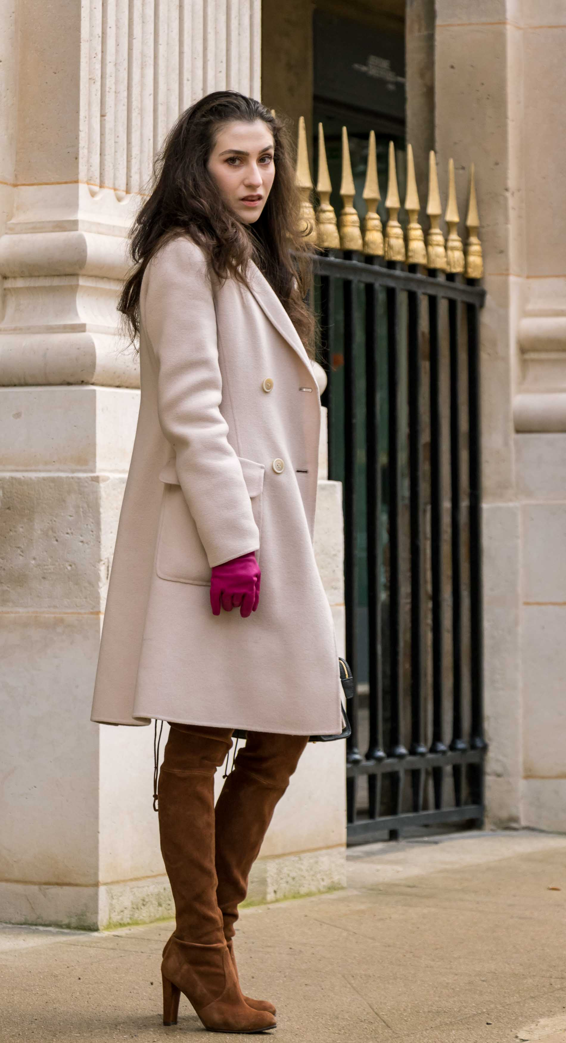 Fashion Blogger Veronika Lipar of Brunette from Wall Street wearing Stuart Weitzman otk boots, Weekend Maxmara coat, pink leather gloves and black small bag during Paris fashion week autumn winter 2018/19 in garden du Palais du Royal