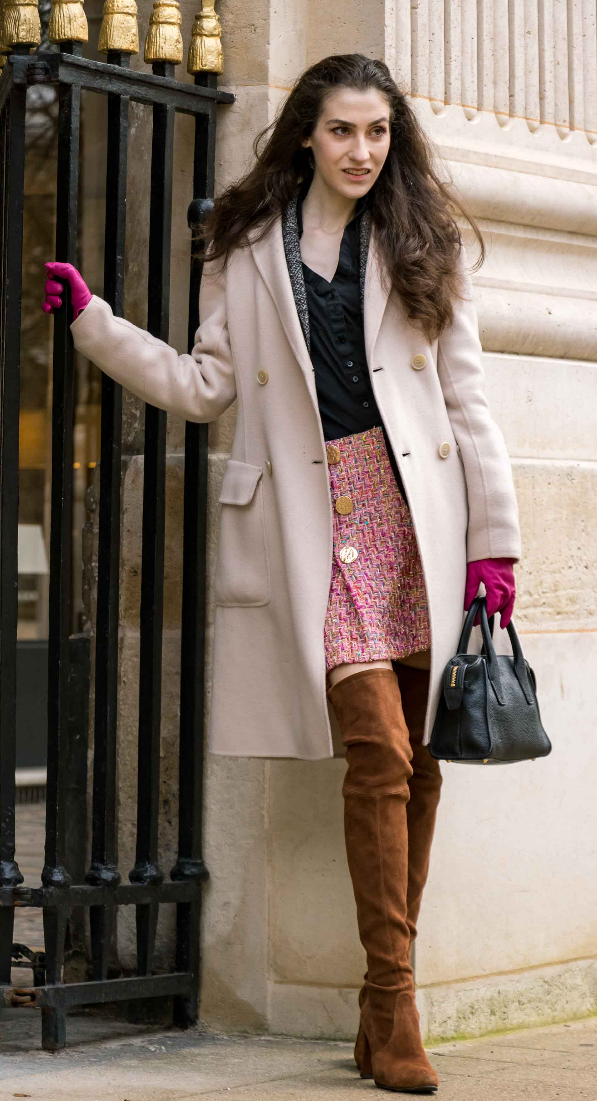 Fashion Blogger Veronika Lipar of Brunette from Wall Street dressed in Stuart Weitzman otk boots, Weekend Maxmara coat, Storets pink tweed shorts, black shirt, pink leather gloves and black small bag during Paris fashion week autumn winter 2018/19 in garden du Palais du Royal