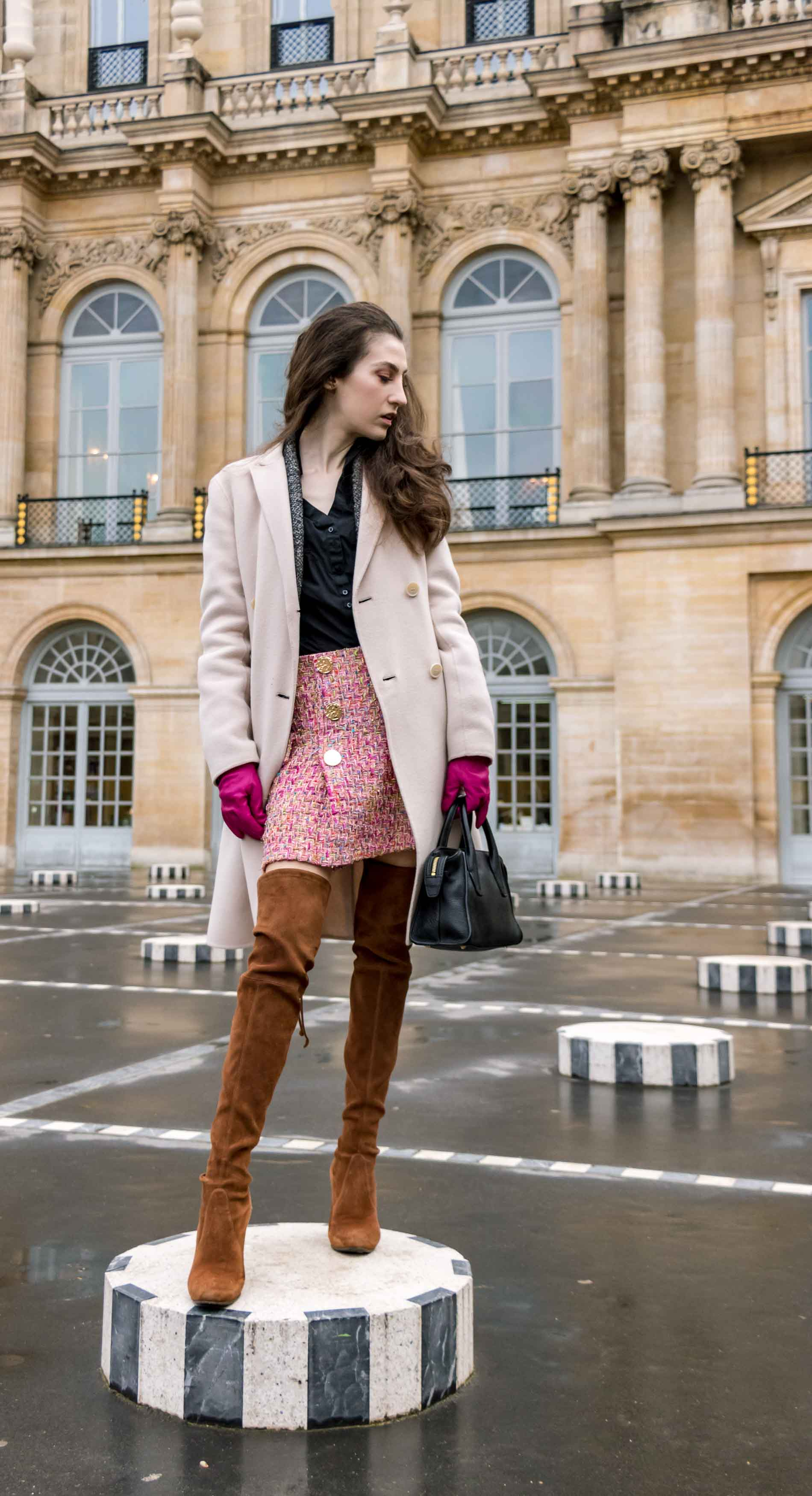 Fashion Blogger Veronika Lipar of Brunette from Wall Street wearing Stuart Weitzman over the knee boots, Weekend Maxmara coat, Storets pink tweed shorts, black shirt, pink leather gloves and black small bag during Paris fashion week autumn winter 2018/19 standing on Les Deux Plateaux