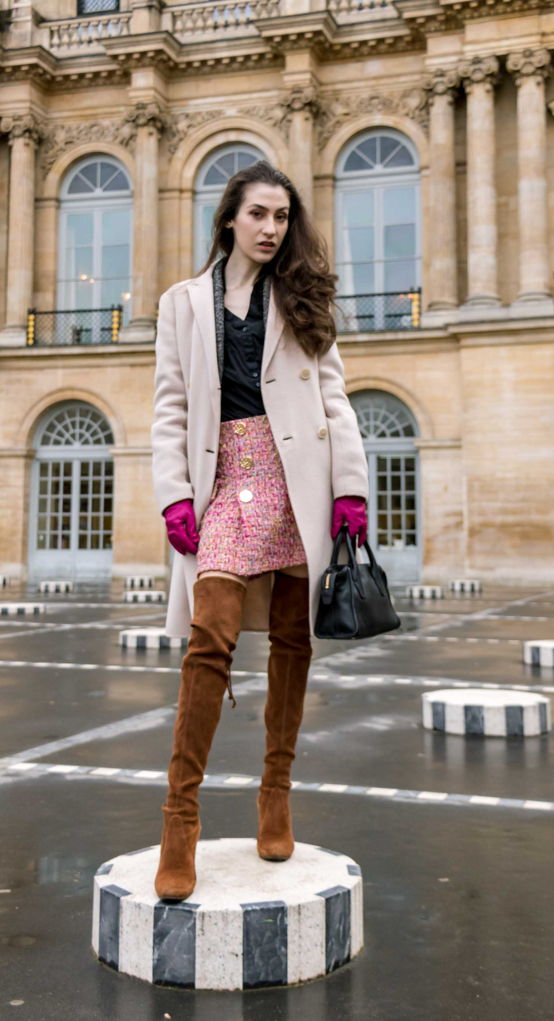 Fashion Blogger Veronika Lipar of Brunette from Wall Street wearing Stuart Weitzman over the knee boots, Weekend Maxmara coat, Storets pink tweed shorts, black shirt, pink leather gloves and black small bag during Paris fashion week autumn winter 2018/19 standing on Les Colonnes de Buren