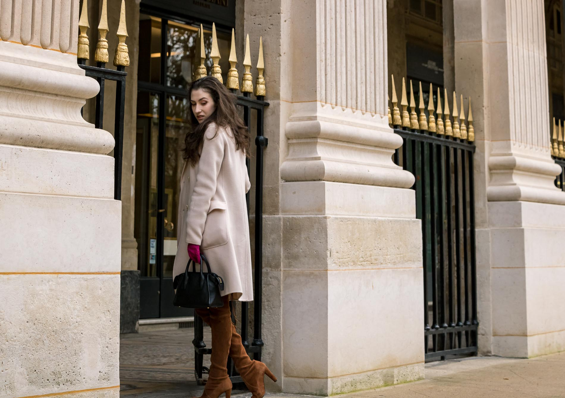 Fashion Blogger Veronika Lipar of Brunette from Wall Street wearing Stuart Weitzman over the knee boots, Weekend Maxmara coat, Storets pink tweed shorts, black shirt, pink leather gloves and black small bag during Paris fashion week autumn winter 2018/19 in garden du Palais du Royal