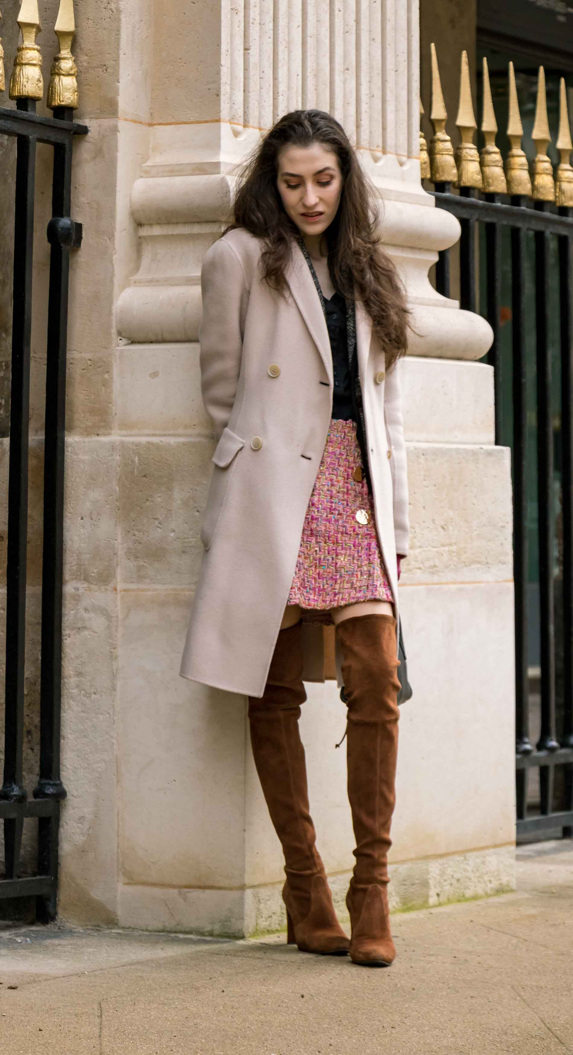 Fashion Blogger Veronika Lipar of Brunette from Wall Street wearing Stuart Weitzman otk boots, Weekend Maxmara coat, Storets pink tweed shorts, black shirt, pink leather gloves and black small bag during Paris fashion week autumn winter 2018/19 in garden du Palais du Royal