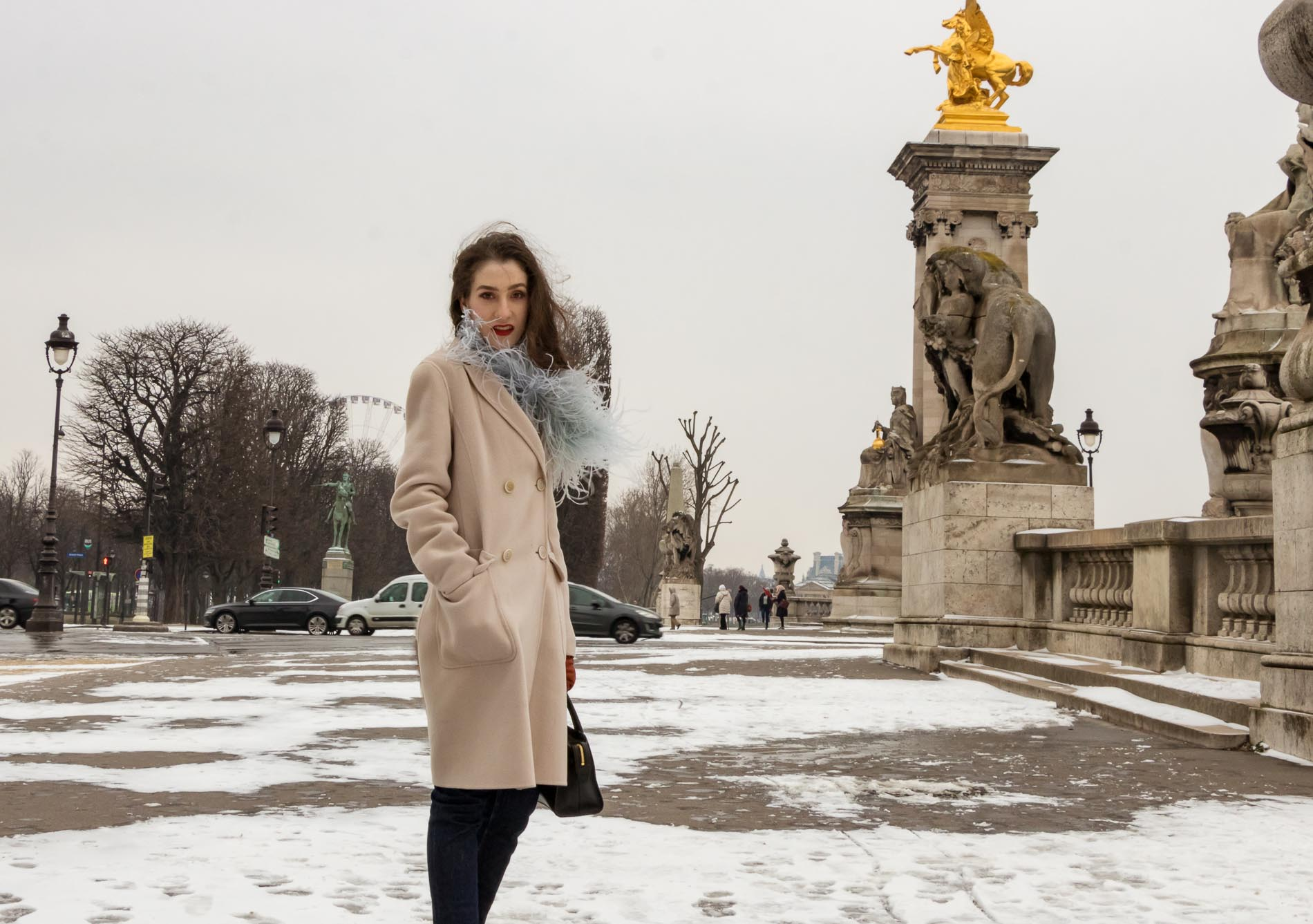 Fashion Blogger Veronika Lipar of Brunette from Wall Street wearing feathers, Weekend Maxmara coat, dark denim jeans, black sock boots, leather gloves, standing at Pont du Alexandre III in Paris during Paris fashion week AW 2018/19