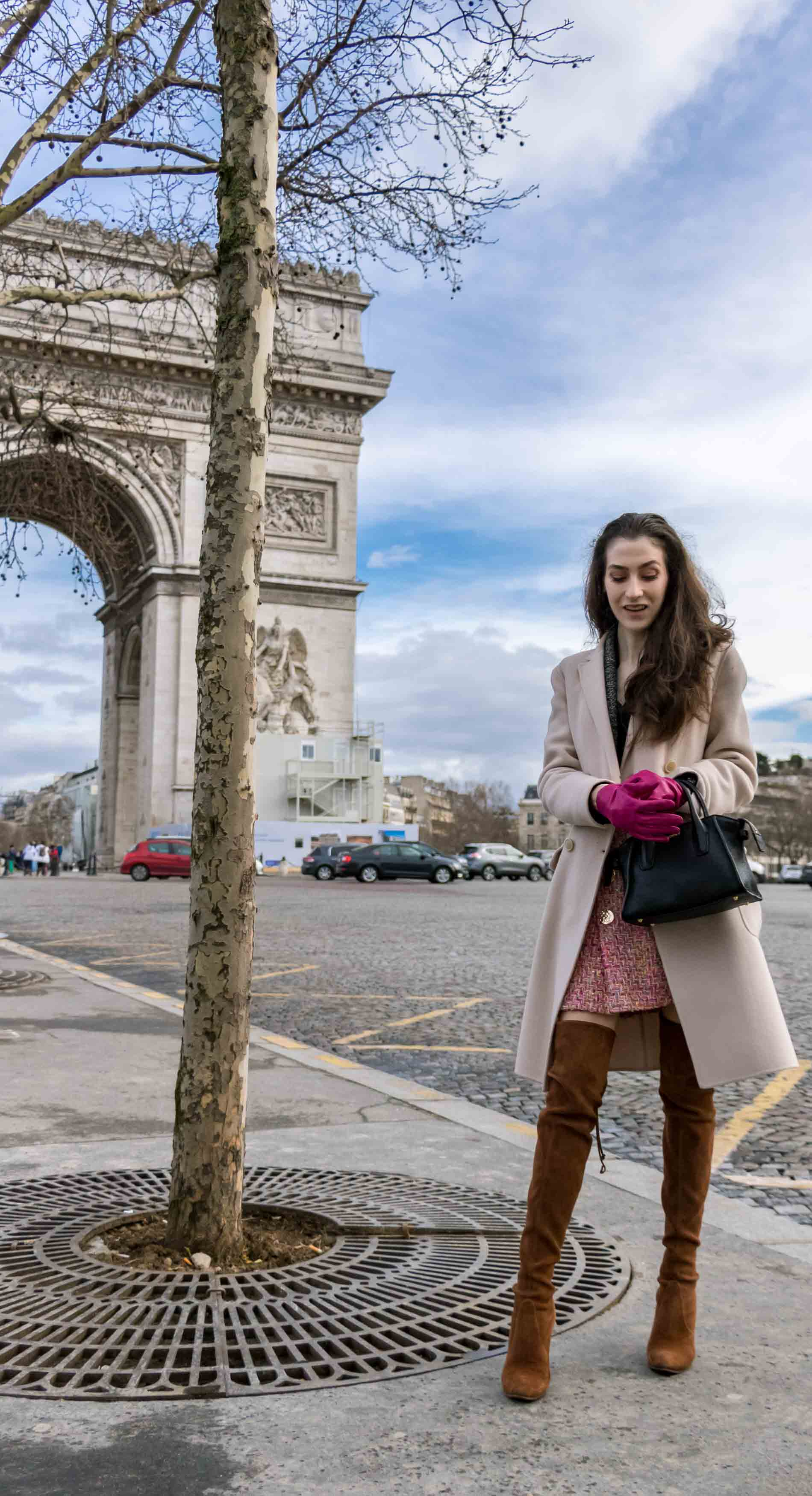 Fashion Blogger Veronika Lipar of Brunette from Wall Street dressed in Stuart Weitzman o tkboots, Weekend Maxmara coat, Storets pink tweed shorts, black shirt, pink leather gloves and black small bag during Paris fashion week autumn winter 2018/19 standing infant of the Arc du Triomphe