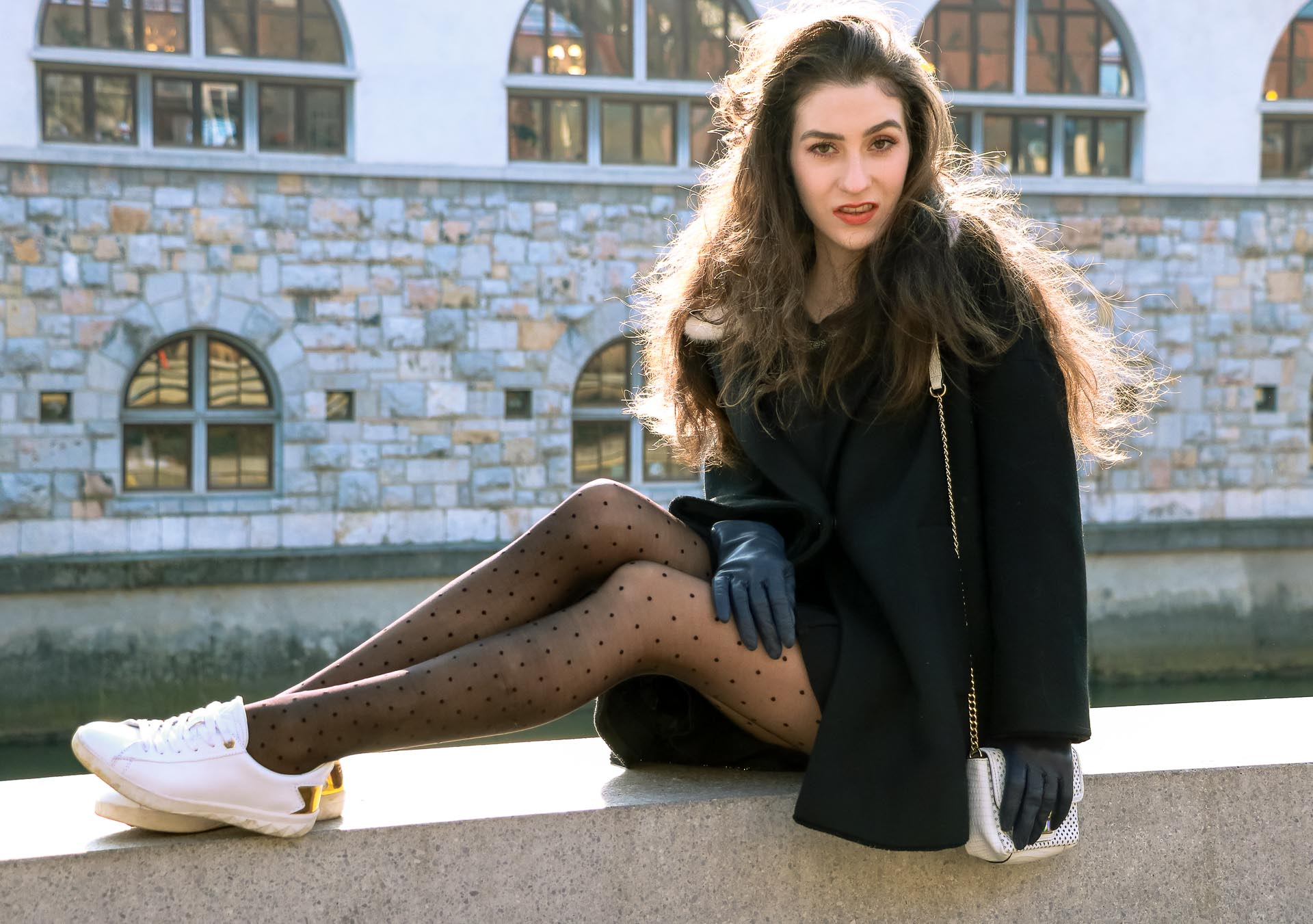 Fashion Blogger Veronika Lipar of Brunette from Wall Street dressed in a black Escada oversized short coat, black mini skirt and white sneakers from Diesel with black polka dot tights and white shoulder chain bag and blue leather gloves while walking on the wall