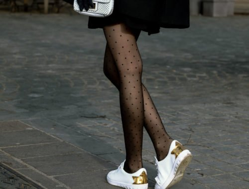 Fashion blogger Veronika Lipar of Brunette from Wall Street wearing black mini skirt, white chain shoulder bag, black sheer polka dot tights, white leather sneakers with golden star