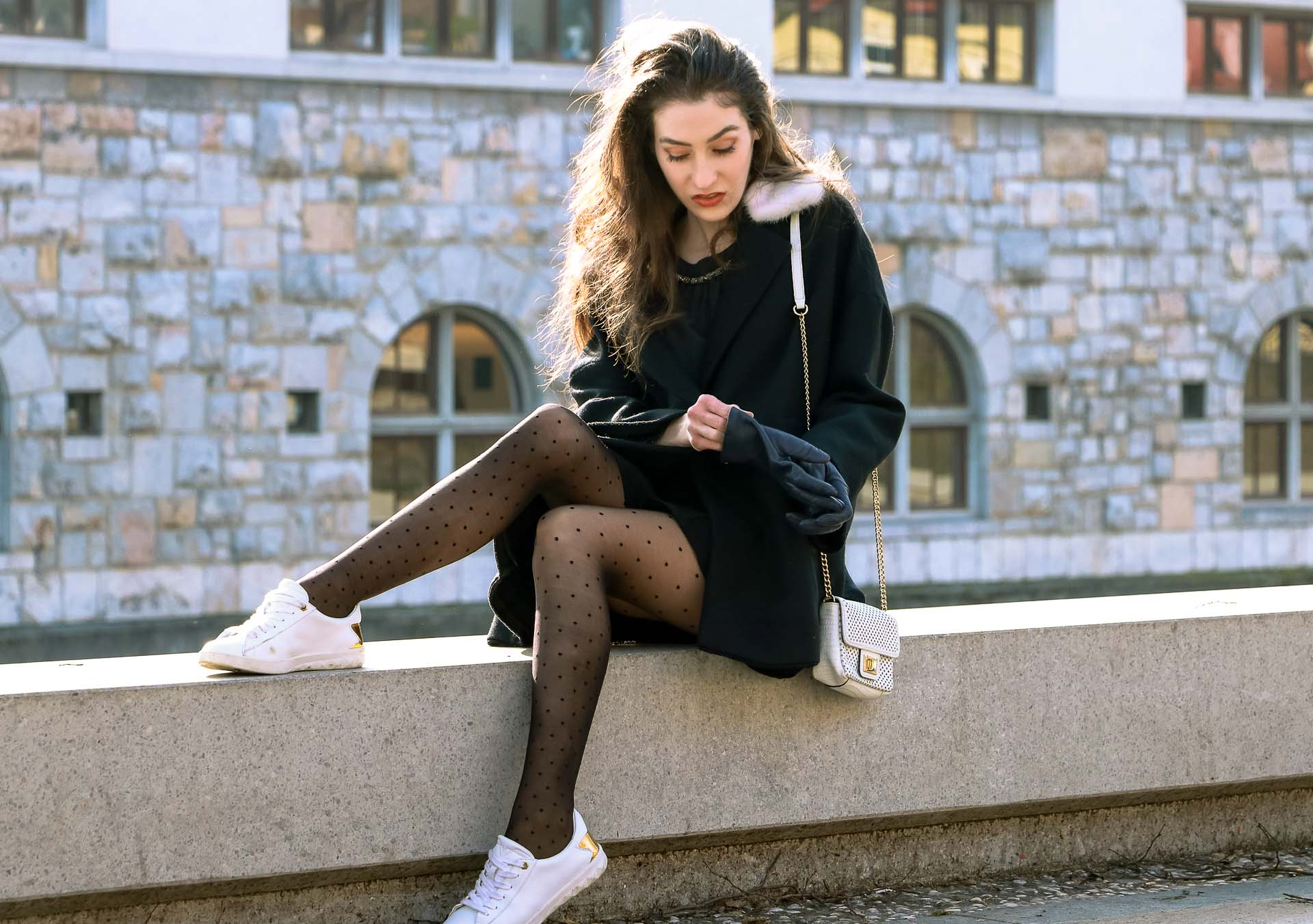 Fashion Blogger Veronika Lipar of Brunette from Wall Street wearing black Escada oversized short coat, black mini skirt and white sneakers from Diesel with black polka dot tights and white shoulder chain bag and blue leather gloves while sitting on a wall
