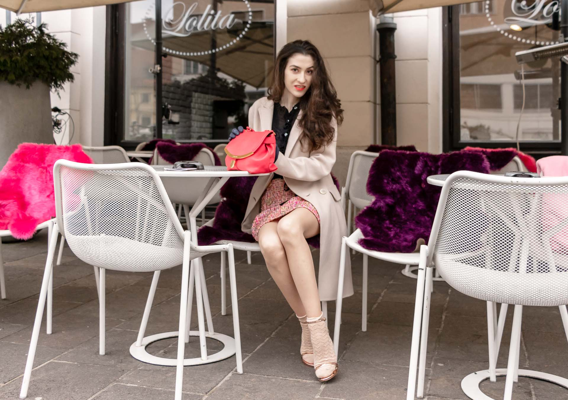 Fashion Blogger Veronika Lipar of Brunette from Wall Street wearing bronze socks and sandals from Stuart Weitzman, tweed Storets mini skirt, black blouse, off white Weekend Maxmara coat while sitting at the caffe