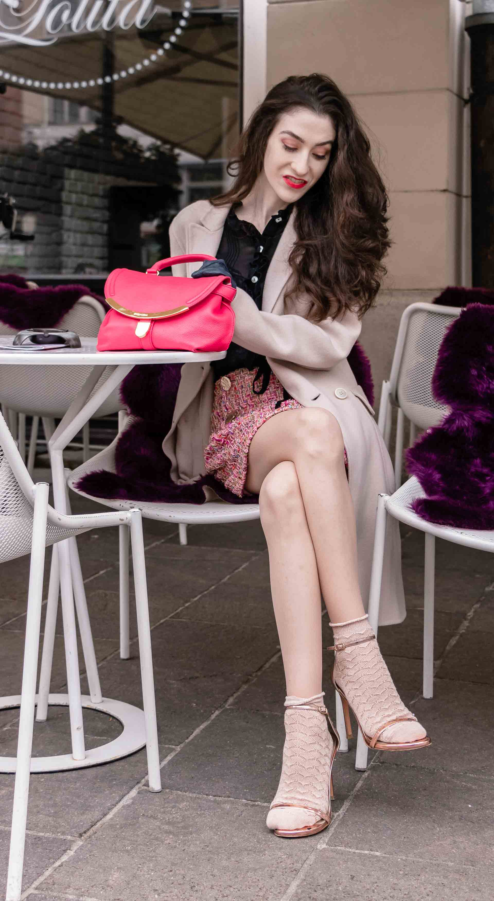 Fashion Blogger Veronika Lipar of Brunette from Wall Street wearing bronze socks and sandals from Stuart Weitzman, tweed Storets mini skirt, black blouse, off white Weekend Maxmara coat while sitting at the caffe waiting for friends
