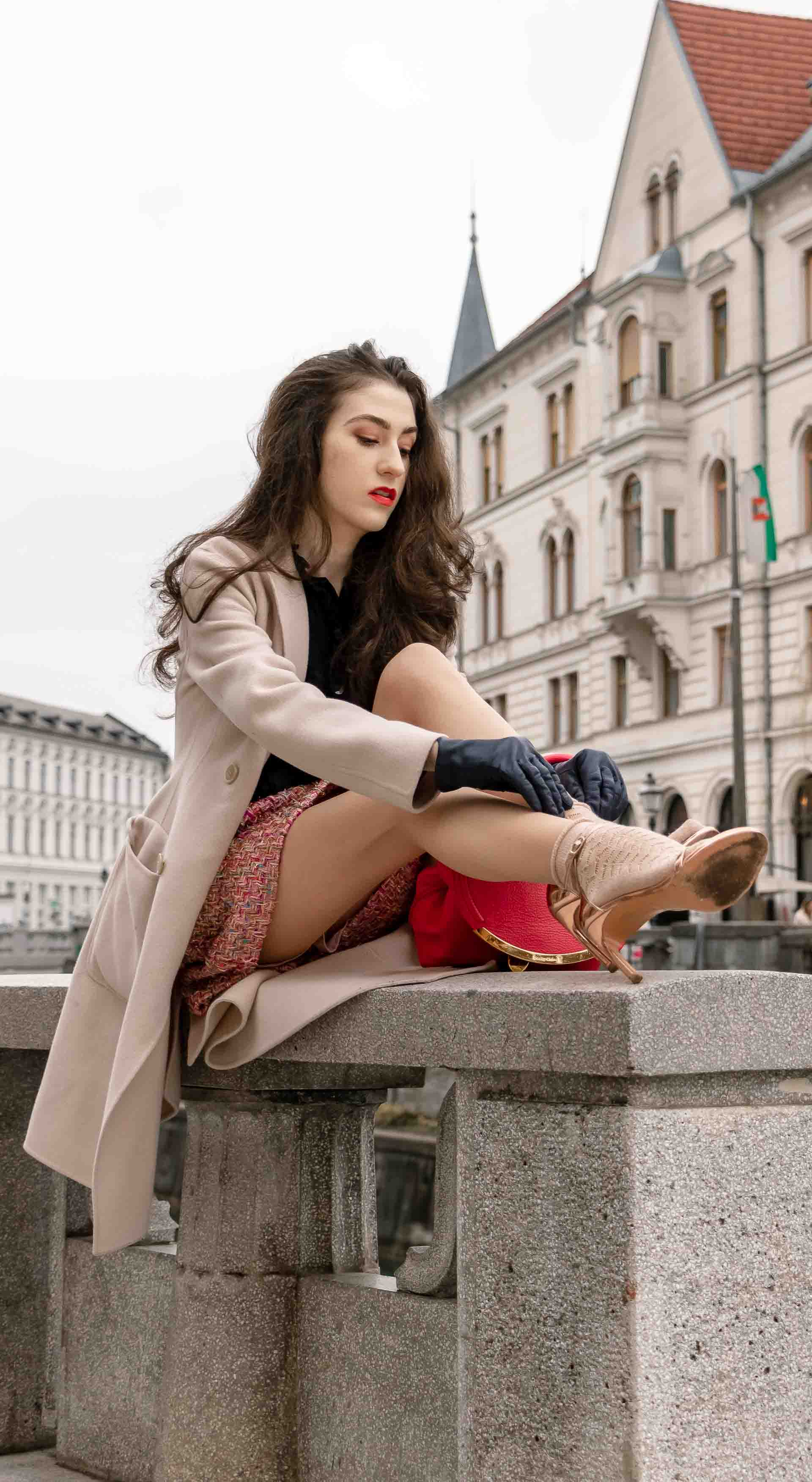 Fashion Blogger Veronika Lipar of Brunette from Wall Street wearing bronze socks and high shine rose gold Songnudist sandals from Stuart Weitzman, tweed Storets minis skirt, black blouse, off white Weekend Maxmara coat while sitting on the wall in Ljubljana