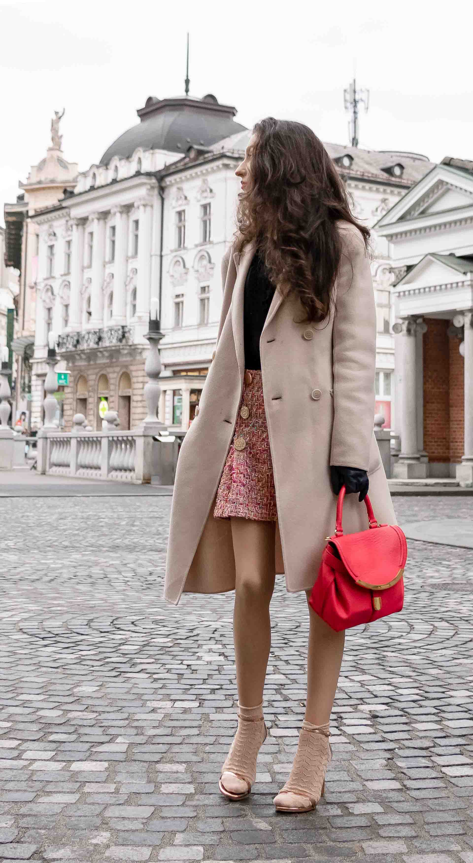 Fashion Blogger Veronika Lipar of Brunette from Wall Street dressed in bronze socks and high shine rose gold Songnudist sandals from Stuart Weitzman, tweed Storets mini skirt, black blouse, off white Weekend Maxmara coat while walking down the street in Ljubljana