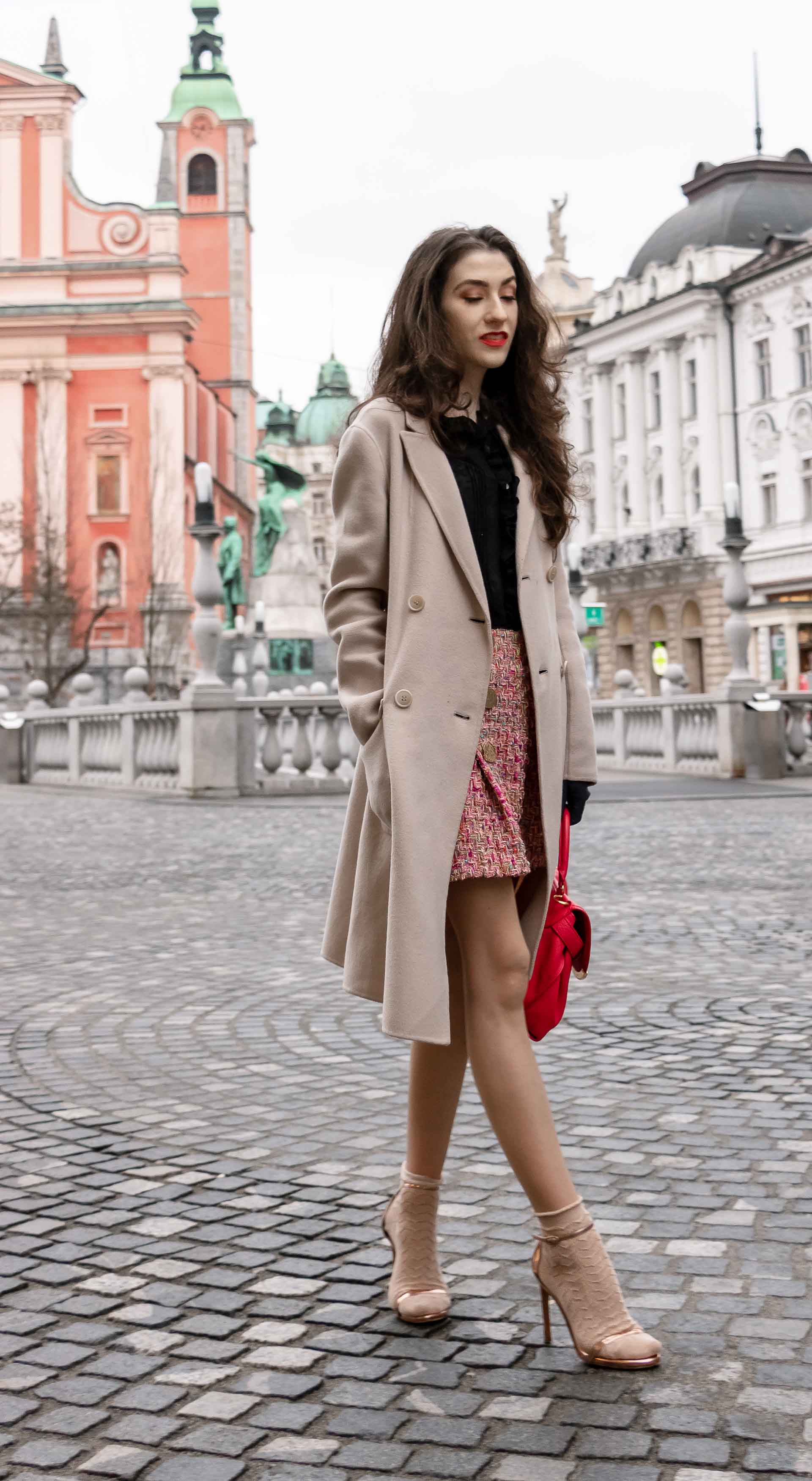 Fashion Blogger Veronika Lipar of Brunette from Wall Street dressed in bronze socks and sandals from Stuart Weitzman, tweed Storets mini skirt, black blouse, off white Weekend Maxmara coat while walking down the street in Ljubljana