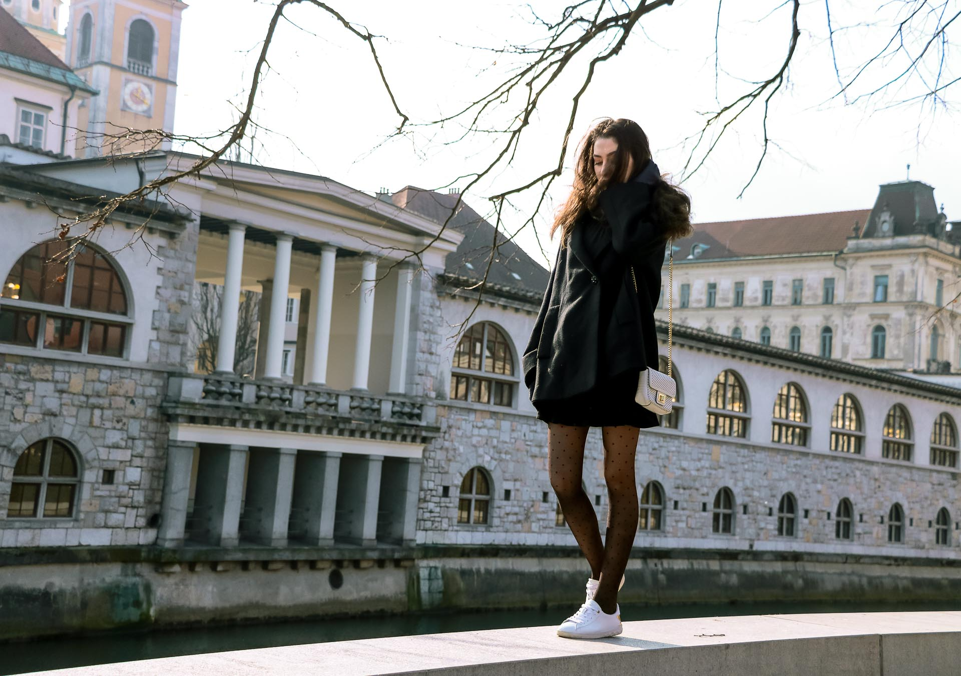 Fashion Blogger Veronika Lipar of Brunette from Wall Street wearing black Escada cape, black mini skirt and white sneakers from Diesel with black polka dot tights and white shoulder chain bag and blue leather gloves while standing on a wall