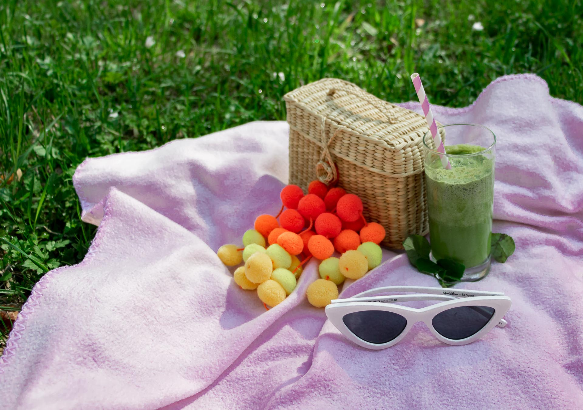 pink picnic blanket, green smoothie, Nannacay pom pom basket bag, Sam Eldeman x Le Specs sunglasses