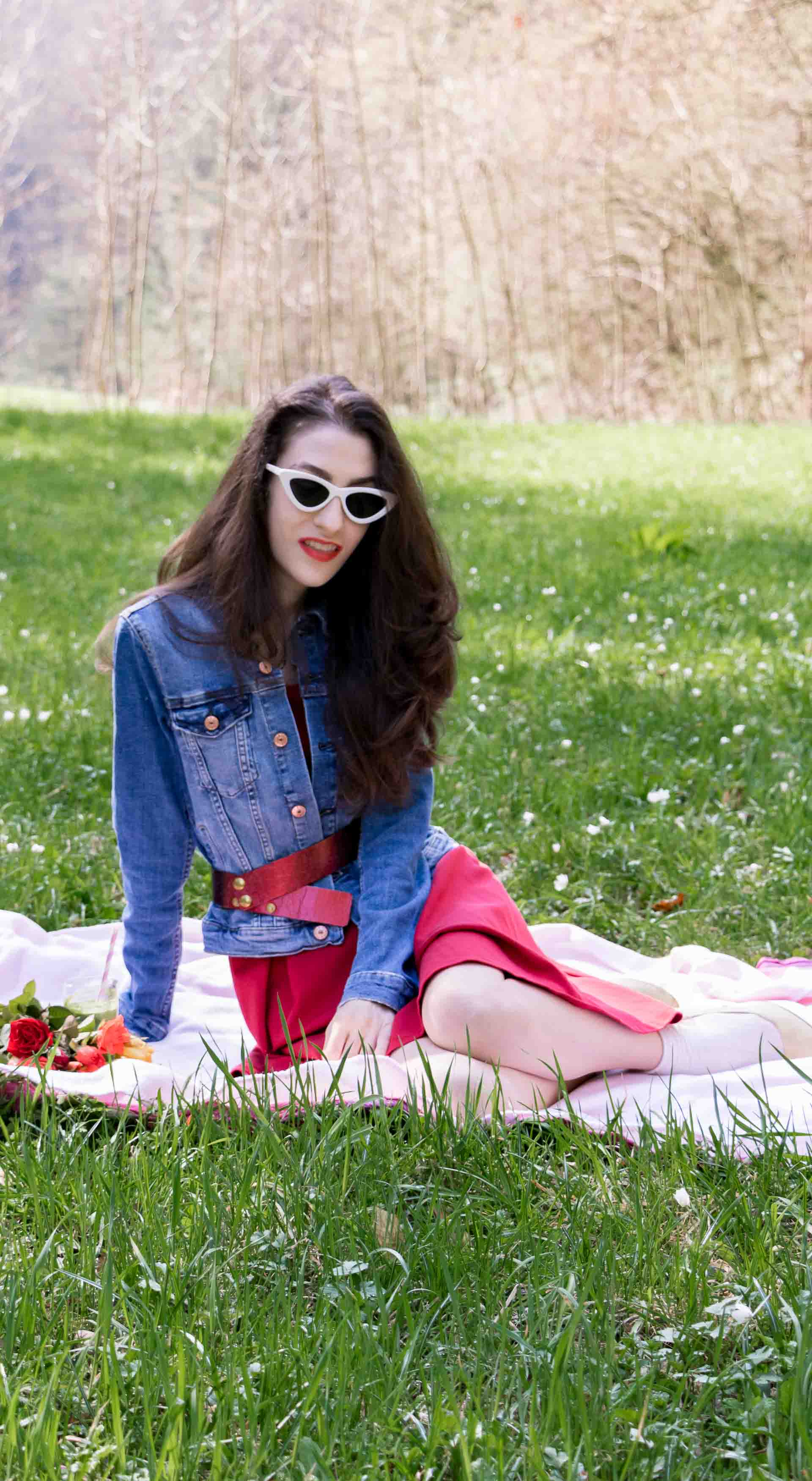 Veronika Lipar Fashion Blogger of Brunette from Wall Street wearing red dress, dangling belt, blue denim jacket, white socks and white pumps, white lolita cat-eye sunglasses from Le Specs, Nannacay raffia basket bag for spring picnic