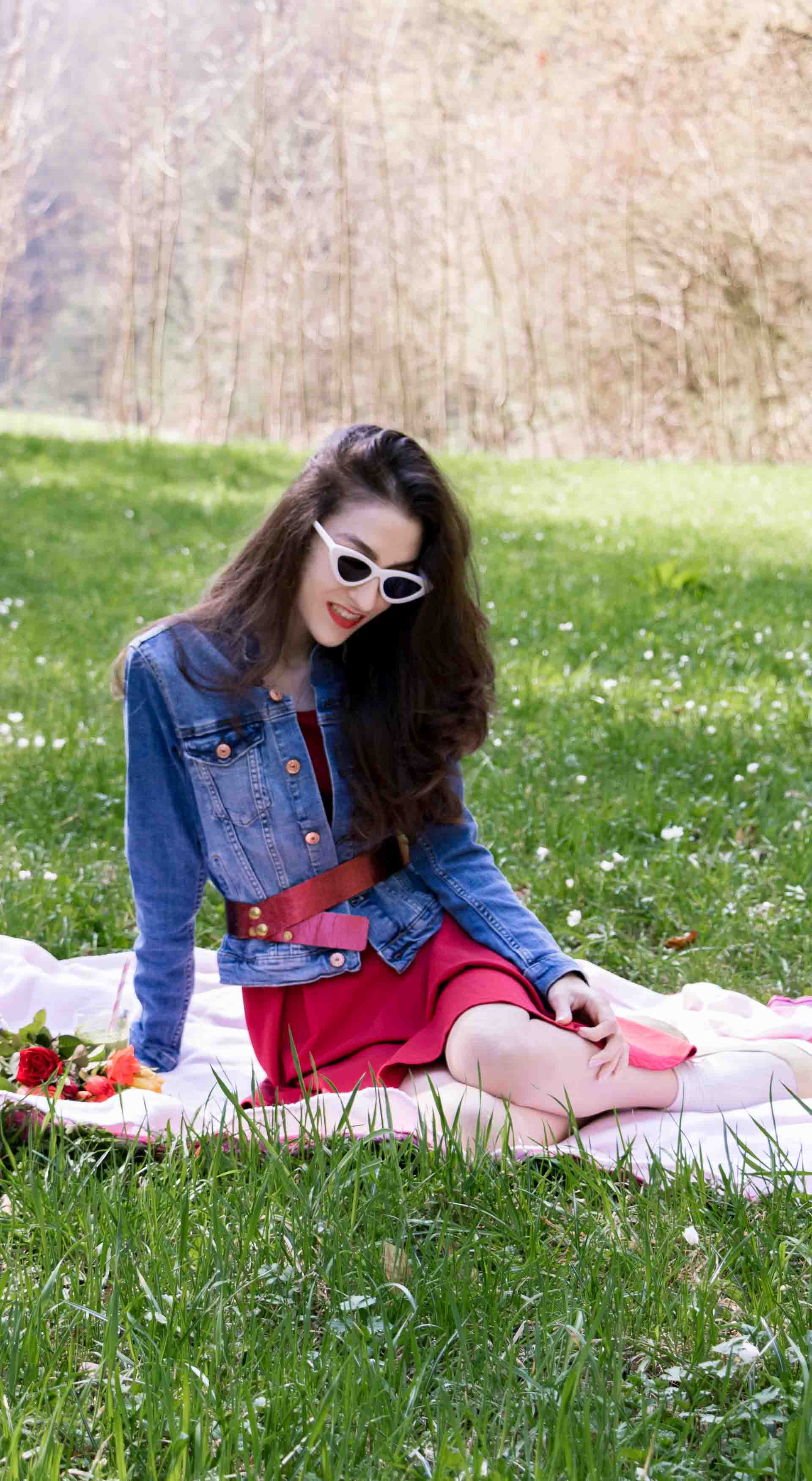 Veronika Lipar Fashion Blogger of Brunette from Wall Street dressed in red dress, dangling belt, blue denim jacket, white socks and white pumps, Sam Eldeman x Le Specs, white lolita cat-eye sunglasses, Nannacay raffia basket bag while sitting on the pink picnic blanket