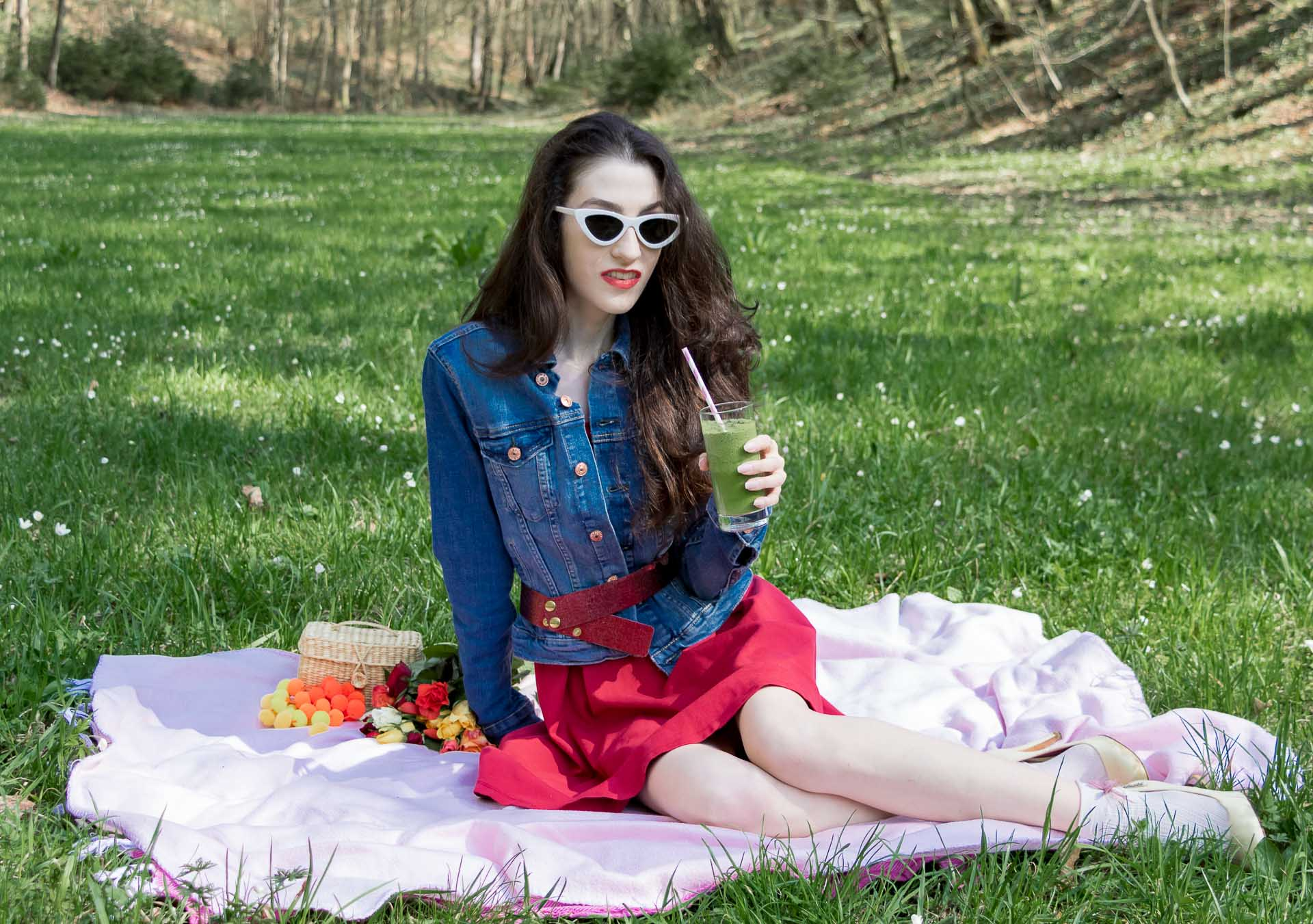 Veronika Lipar Fashion Blogger of Brunette from Wall Street wearing red dress, dangling belt, blue denim jacket, white socks and white pumps, white lolita cat-eye sunglasses from Le Specs, Nannacay raffia basket bag while drinking green smoothie on the pink picnic blanket