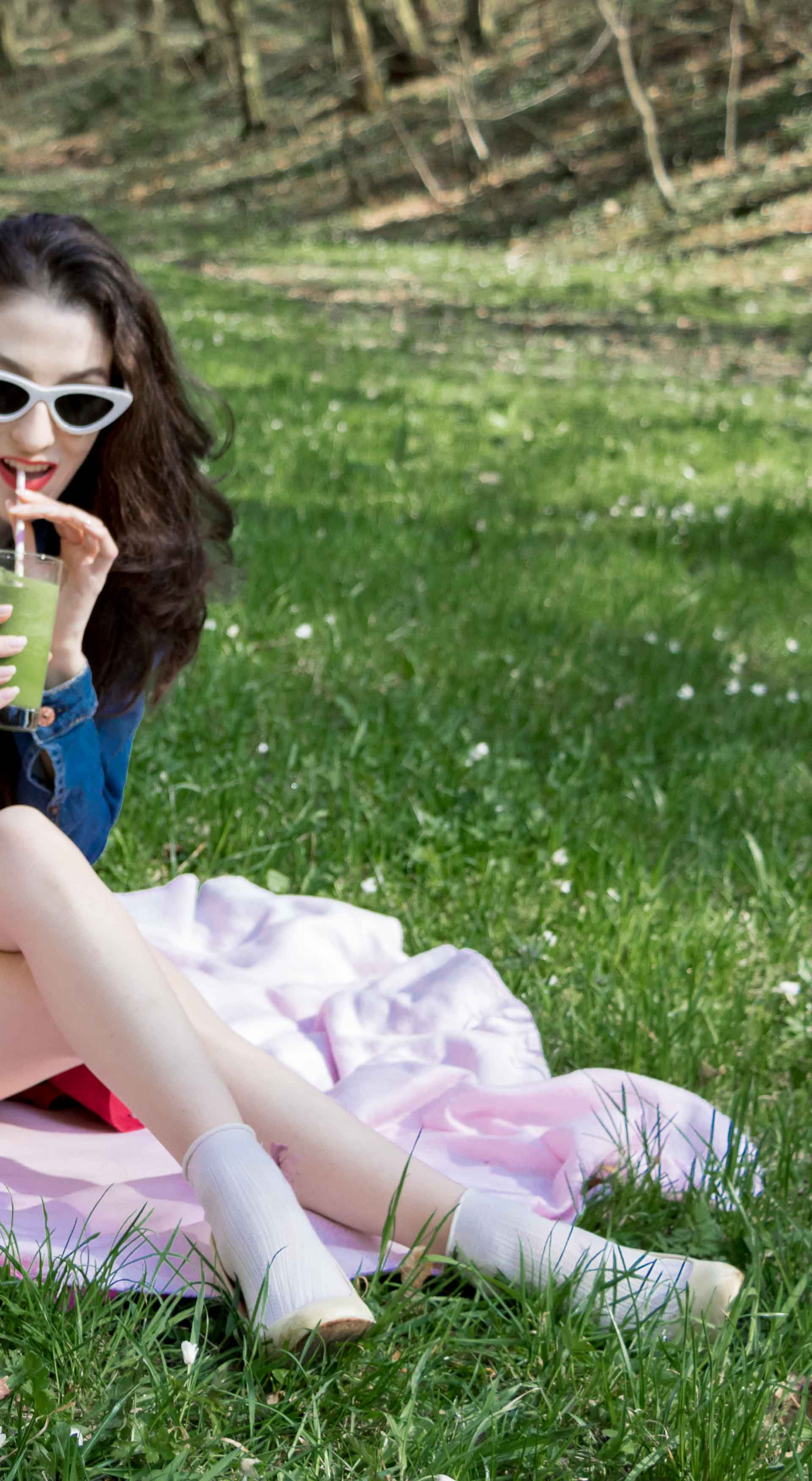Veronika Lipar Fashion Blogger of Brunette from Wall Street wearing red dress, dangling belt, blue denim jacket, white socks and white pumps, white lolita cat-eye sunglasses from Le Specs, Nannacay raffia basket bag while sitting on the pink picnic blanket