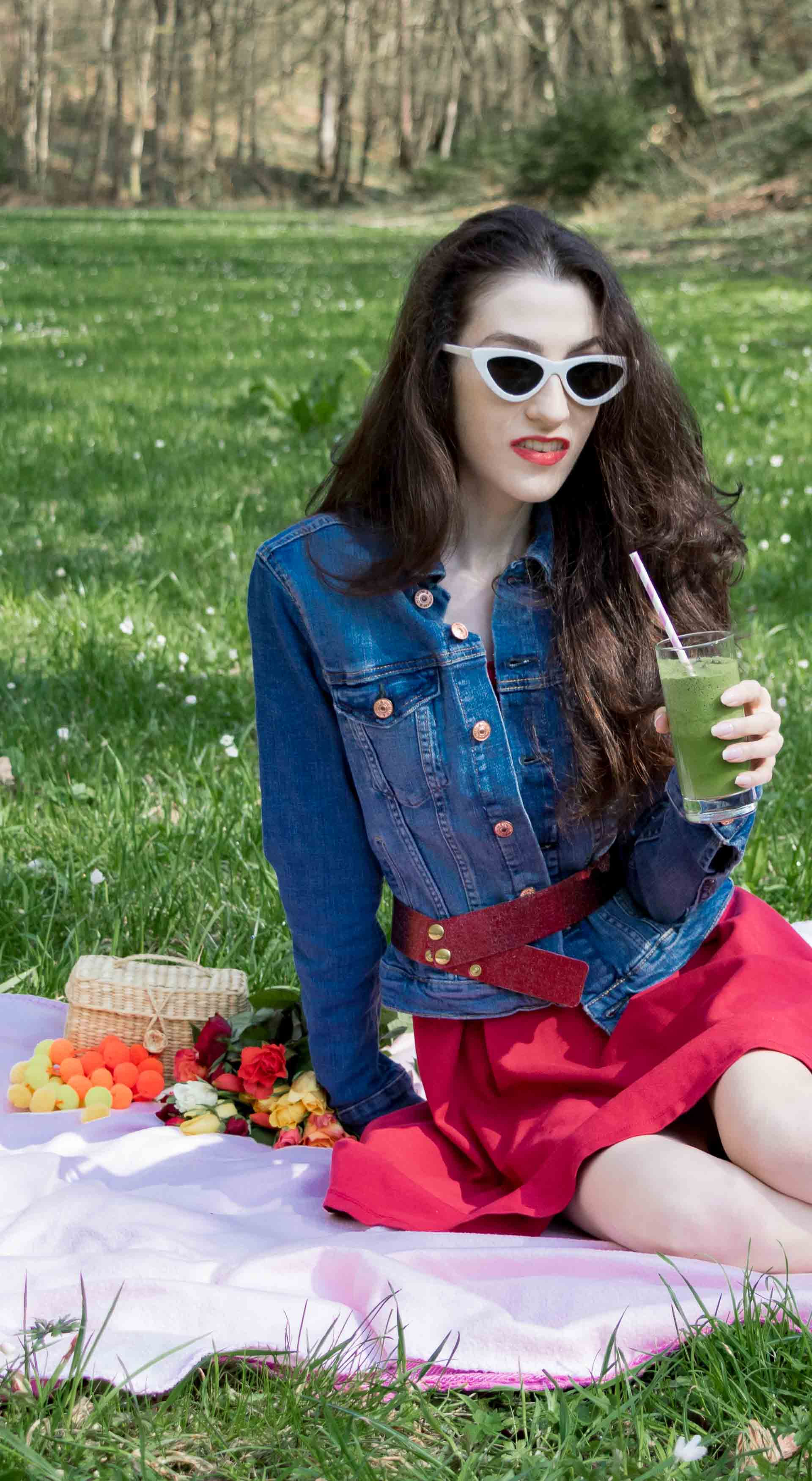 Veronika Lipar Fashion Blogger of Brunette from Wall Street dressed in red dress, dangling belt, blue denim jacket, white socks and white pumps, white lolita cat-eye sunglasses from Le Specs, Nannacay raffia basket bag while drinking green smoothie on the pink picnic blanket