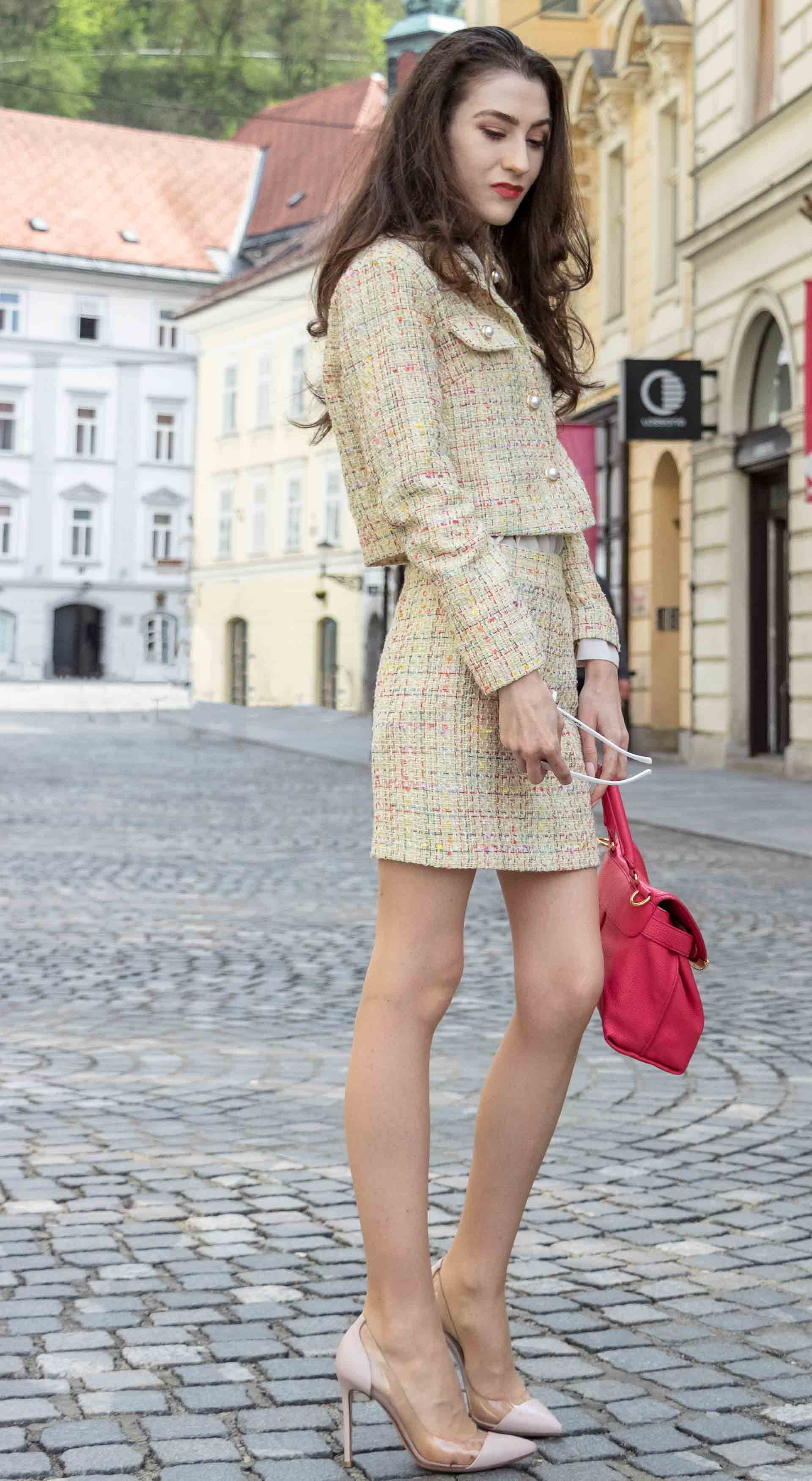 Fashion Blogger Veronika Lipar of Brunette from Wall Street dressed in Storets yellow tweed mini skirt suit, Gianvito Rossi plexi pumps, See by Chloe pink top handle bag, Adam Selman x Lespecs white Lolita sunglasses standing on the street in Ljubljana