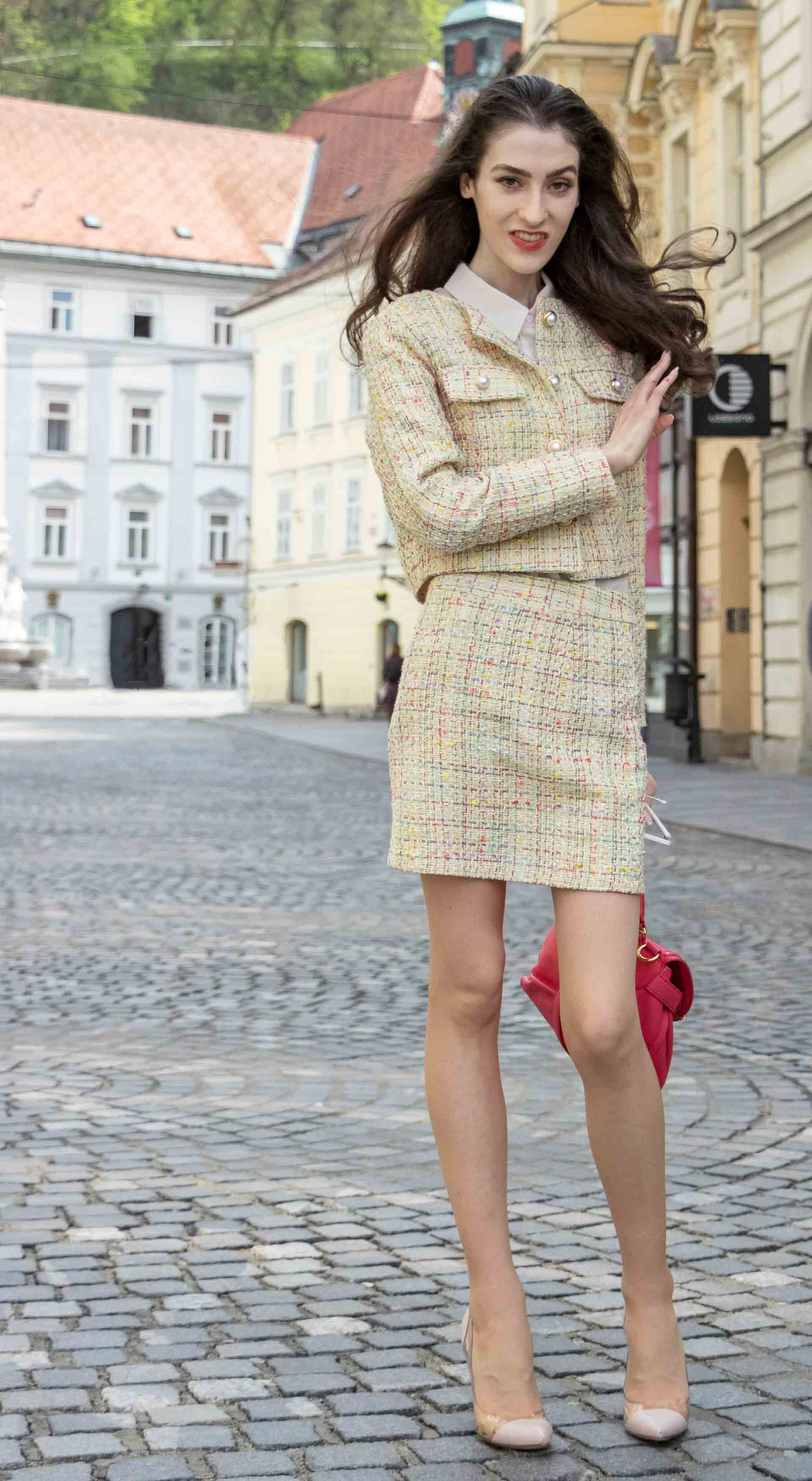 Fashion Blogger Veronika Lipar of Brunette from Wall Street dressed in Storets yellow tweed mini skirt suit, Gianvito Rossi plexi pumps, See by Chloe pink top handle bag, Adam Selman x Lespecs white Lolita sunglasses on the streets in Ljubljana