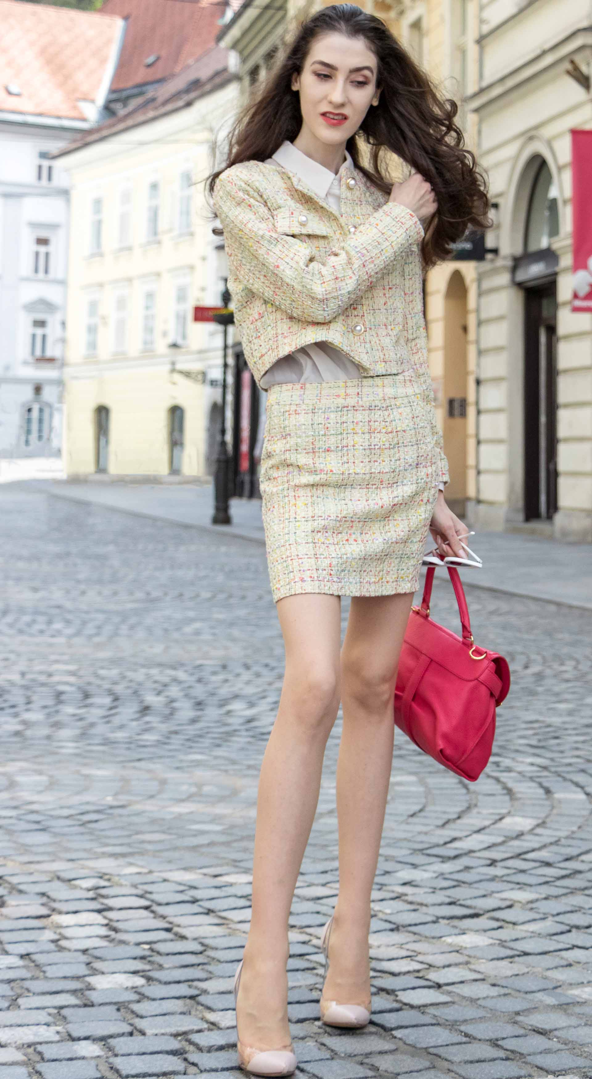 Fashion Blogger Veronika Lipar of Brunette from Wall Street dressed in Storets yellow tweed mini skirt suit, Gianvito Rossi plexi pumps, See by Chloe pink top handle bag on the streets in Ljubljana flipping hair