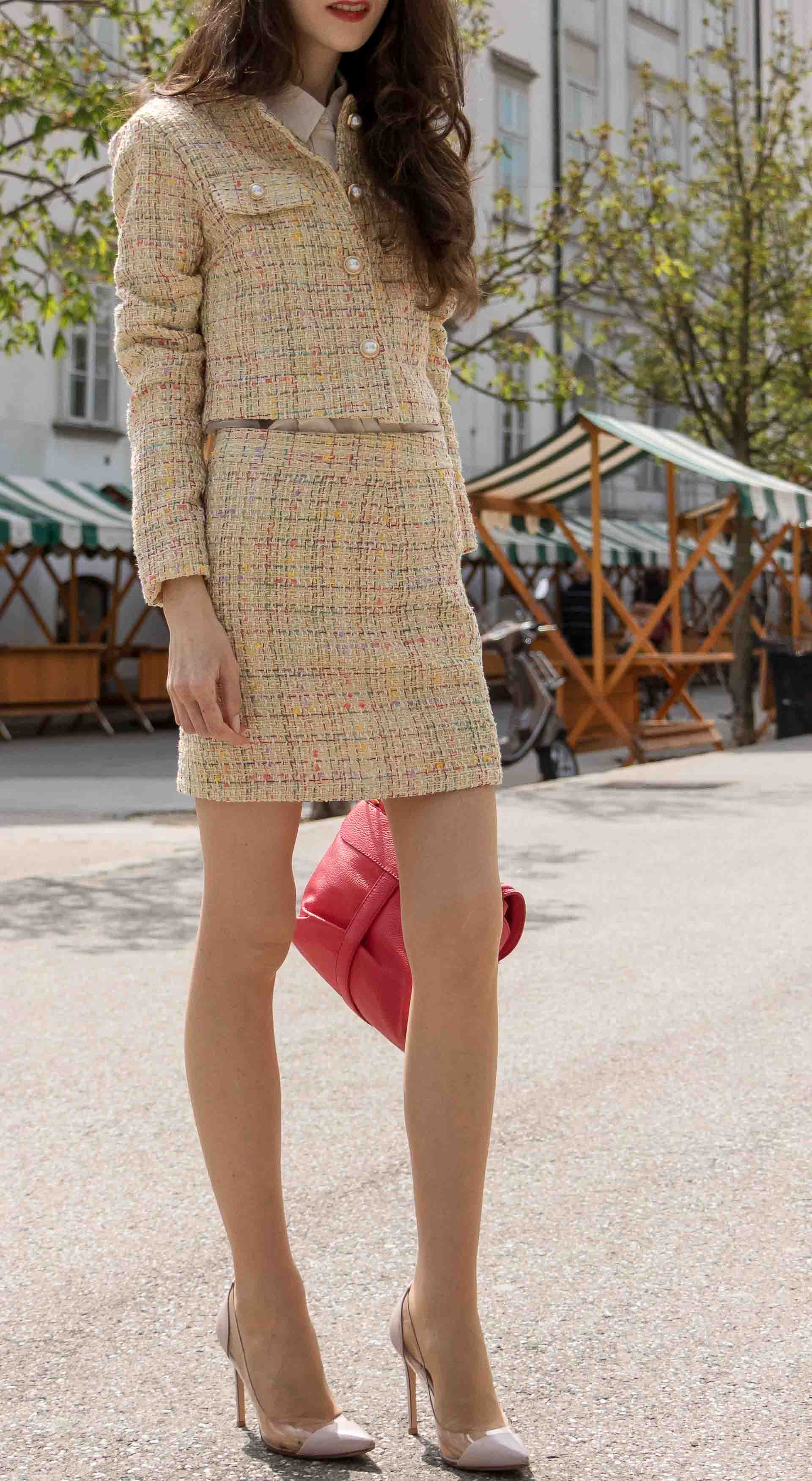 Fashion Blogger Veronika Lipar of Brunette from Wall Street wearing Storets yellow tweed mini skirt suit, Gianvito Rossi plexi pumps, See by Chloe pink top handle bag, Adam Selman x Lespecs white Lolita sunglasses standing on the street in Ljubljana Slovenia