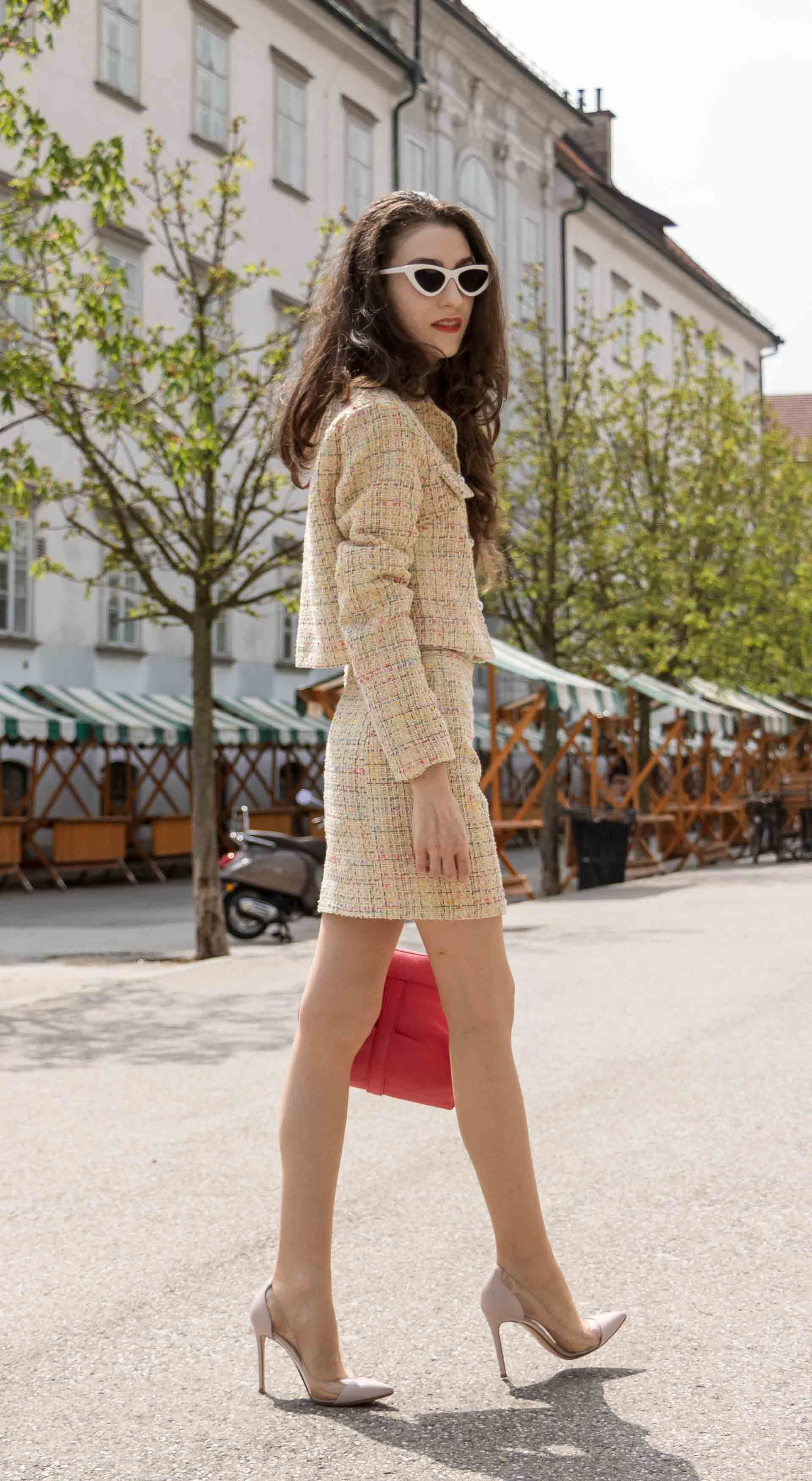 Fashion Blogger Veronika Lipar of Brunette from Wall Street wearing Storets yellow tweed mini skirt suit, Gianvito Rossi plexi pumps, See by Chloe pink top handle bag, Adam Selman x Lespecs white Lolita sunglasses walking on the street in Ljubljana