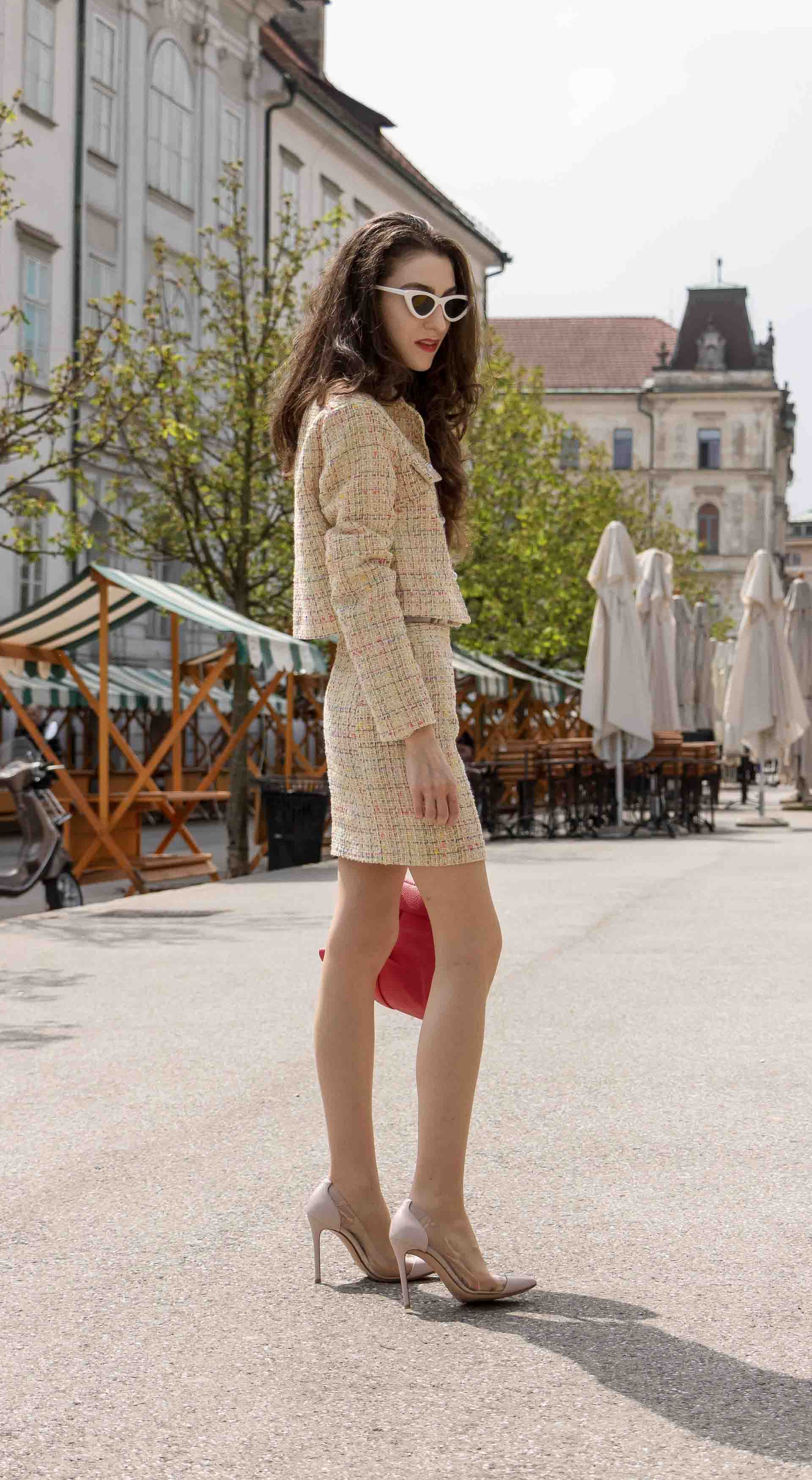 Fashion Blogger Veronika Lipar of Brunette from Wall Street wearing Storets yellow tweed mini skirt suit, Gianvito Rossi plexi pumps, See by Chloe pink top handle bag, Adam Selman x Lespecs white Lolita sunglasses walking on the street in Ljubljana Slovenia
