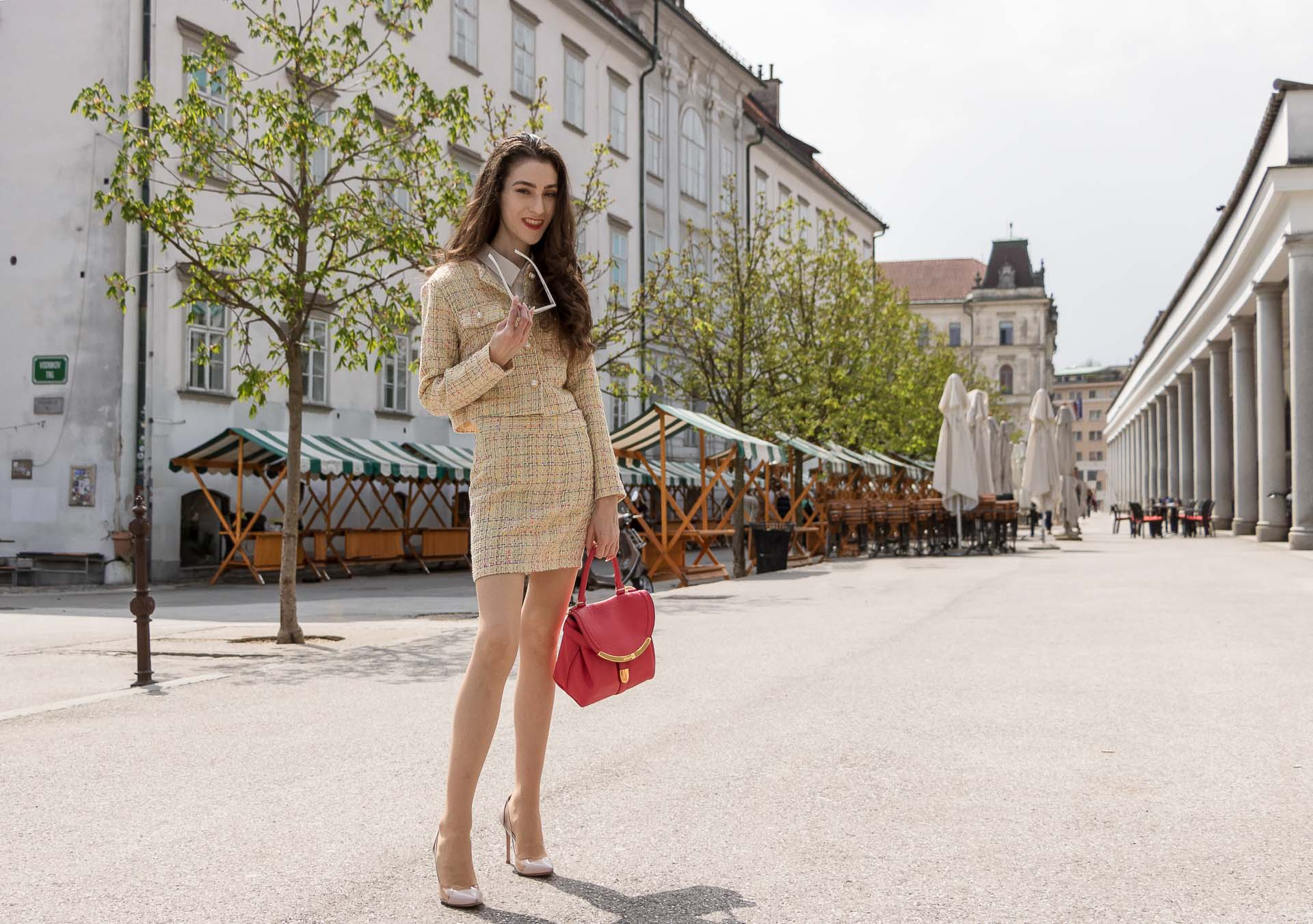 Fashion Blogger Veronika Lipar of Brunette from Wall Street wearing Storets yellow tweed mini skirt suit, Gianvito Rossi plexi pumps, See by Chloe pink top handle bag standing on the street in Ljubljana