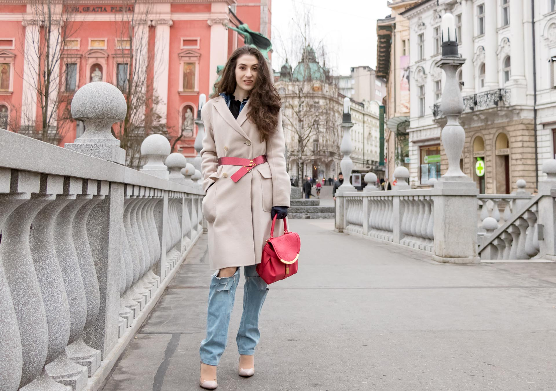 Fashion Blogger Veronika Lipar of Brunette from Wall Street dressed in distressed blue Levi's jeans, off-white double breasted Weekend Maxmara coat, red dangling belt, blush Gianvito Rossi plexi pumps, See by Chloe pink top handle bag, blue leather gloves on the bridge of Ljubljana