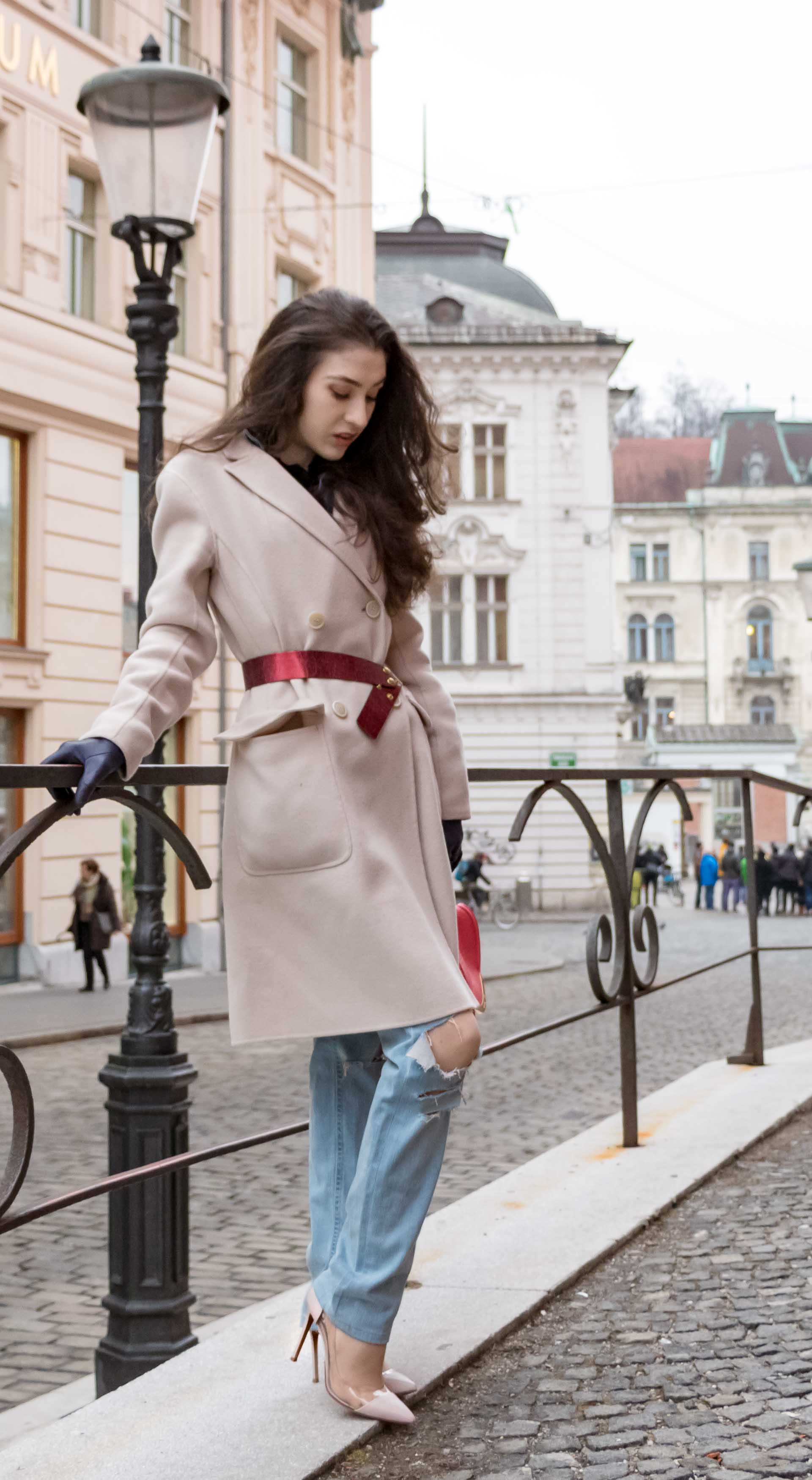 Fashion Blogger Veronika Lipar of Brunette from Wall Street wearing ripped blue Levi's jeans, off-white double breasted Weekend Maxmara coat, red dangling belt, blush Gianvito Rossi plexi pumps, See by Chloe pink top handle bag, blue leather gloves leaning on the fence on the street of Ljubljana