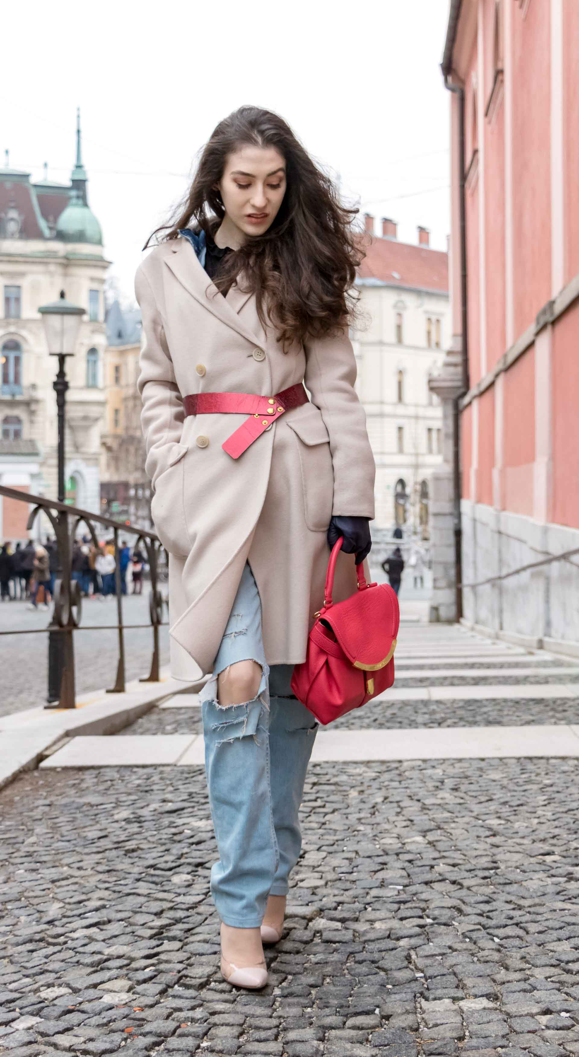 Fashion Blogger Veronika Lipar of Brunette from Wall Street wearing distressed blue Levi's jeans, off-white double breasted Weekend Maxmara coat, red dangling belt, blush Gianvito Rossi plexi pumps, See by Chloe pink top handle bag, blue leather gloves leaning on the wall of the bridge in Ljubljana