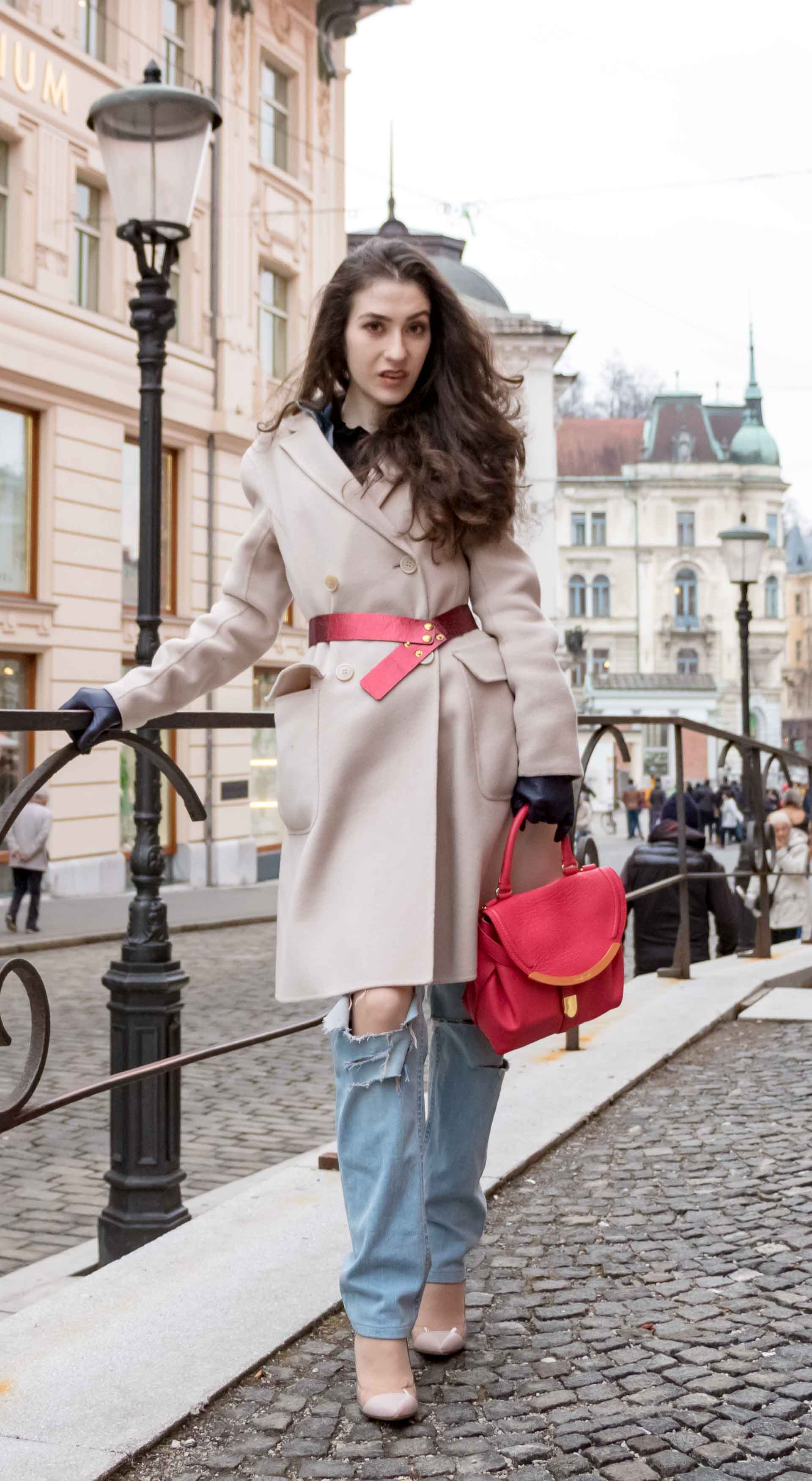 Fashion Blogger Veronika Lipar of Brunette from Wall Street wearing distressed blue Levi's jeans, off-white double breasted Weekend Maxmara coat, red dangling belt, blush Gianvito Rossi plexi pumps, See by Chloe pink top handle bag, blue leather gloves leaning on the fence on the street of Ljubljana