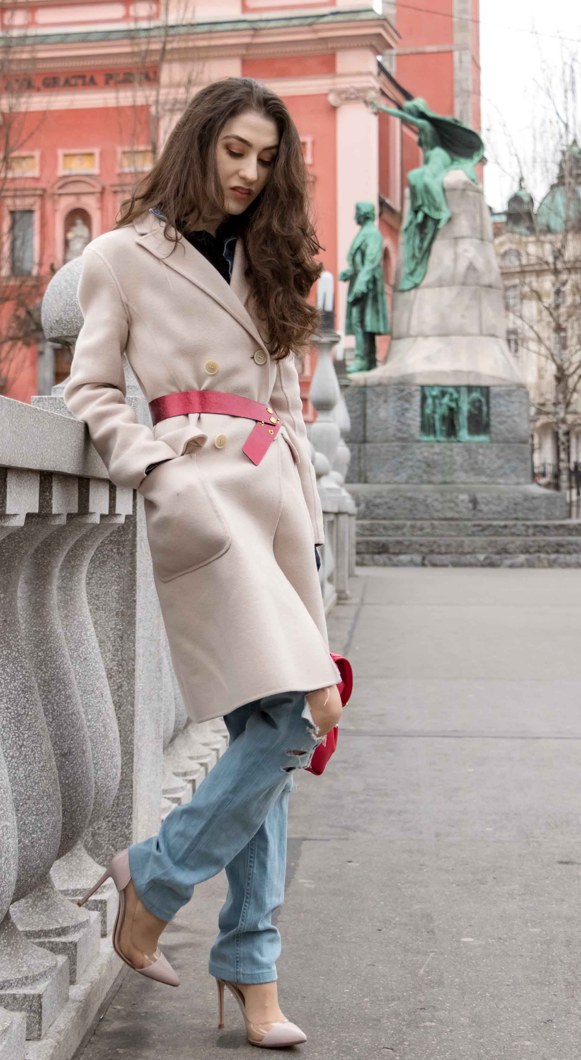 Fashion Blogger Veronika Lipar of Brunette from Wall Street wearing ripped blue Levi's jeans, off-white double breasted Weekend Maxmara coat, red dangling belt, blush Gianvito Rossi plexi pumps, See by Chloe pink top handle bag, blue leather gloves leaning on the wall of the bridge in Ljubljana