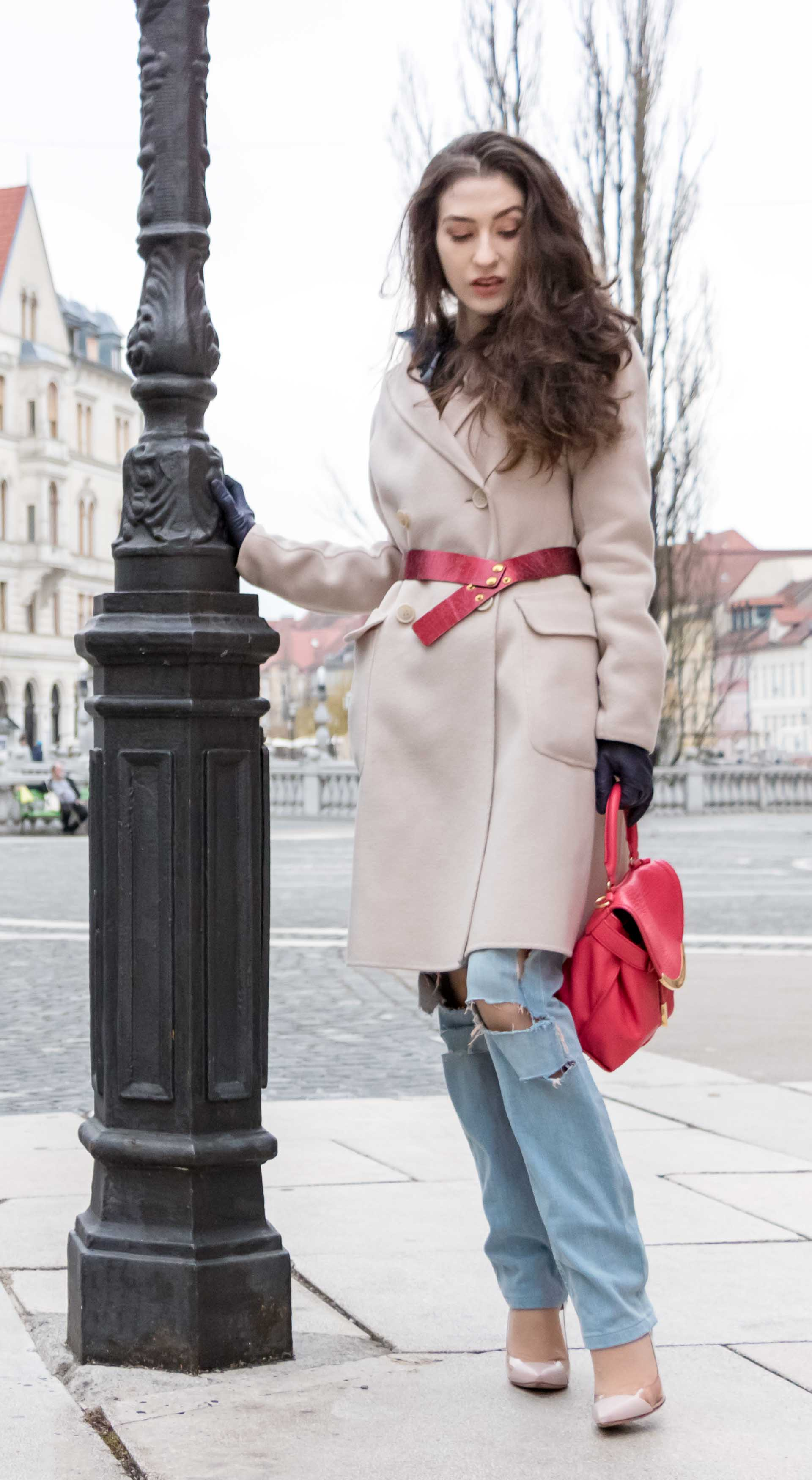 Fashion Blogger Veronika Lipar of Brunette from Wall Street wearing distressed blue Levi's jeans, off-white double breasted Weekend Maxmara coat, red dangling belt, blush Gianvito Rossi plexi pumps, See by Chloe pink top handle bag, blue leather gloves leaning on street lamp in Ljubljana