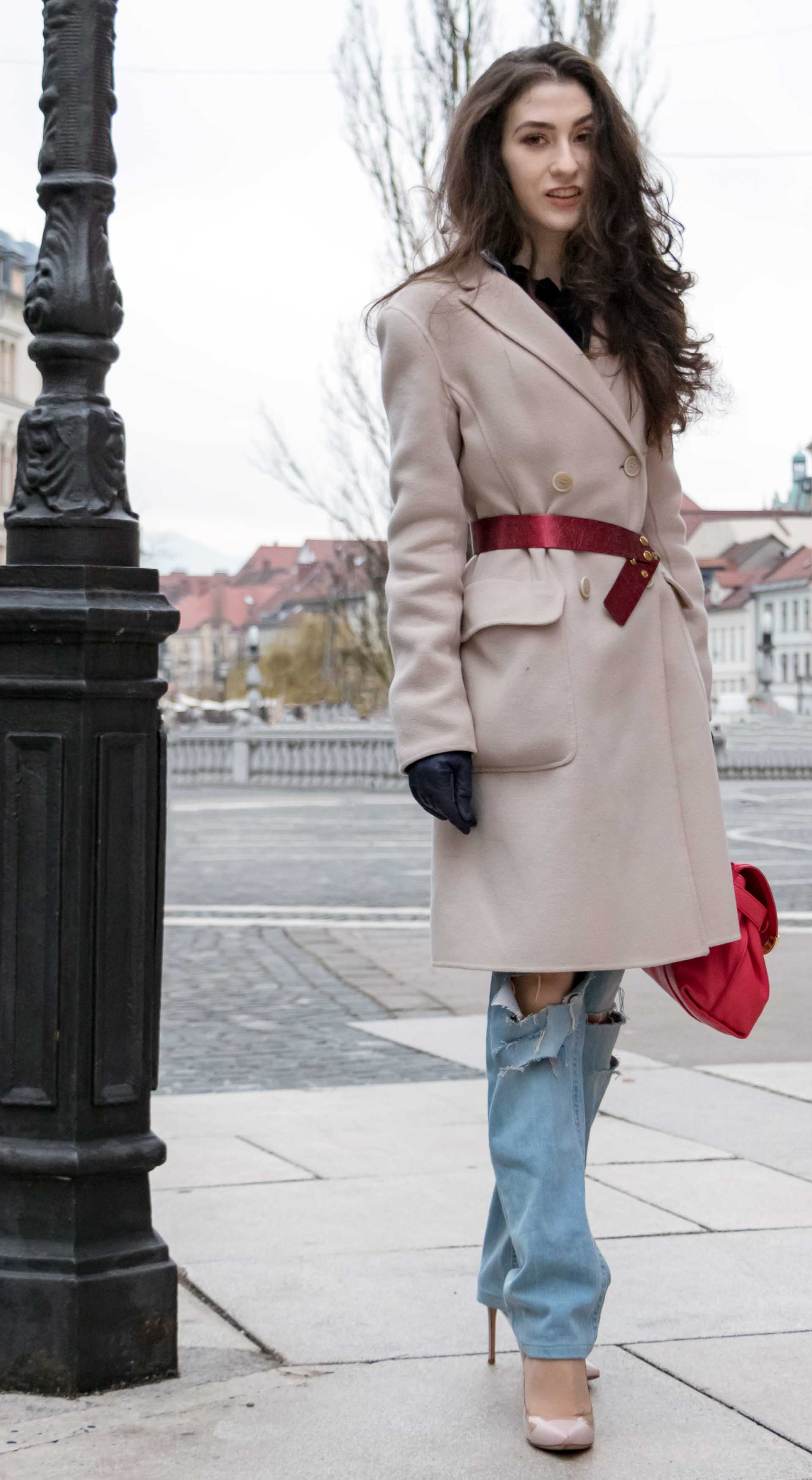 Fashion Blogger Veronika Lipar of Brunette from Wall Street dressed in distressed blue Levi's jeans, off-white double breasted Weekend Maxmara coat, red dangling belt, blush Gianvito Rossi plexi pumps, See by Chloe pink top handle bag, blue leather gloves on the street of Ljubljana