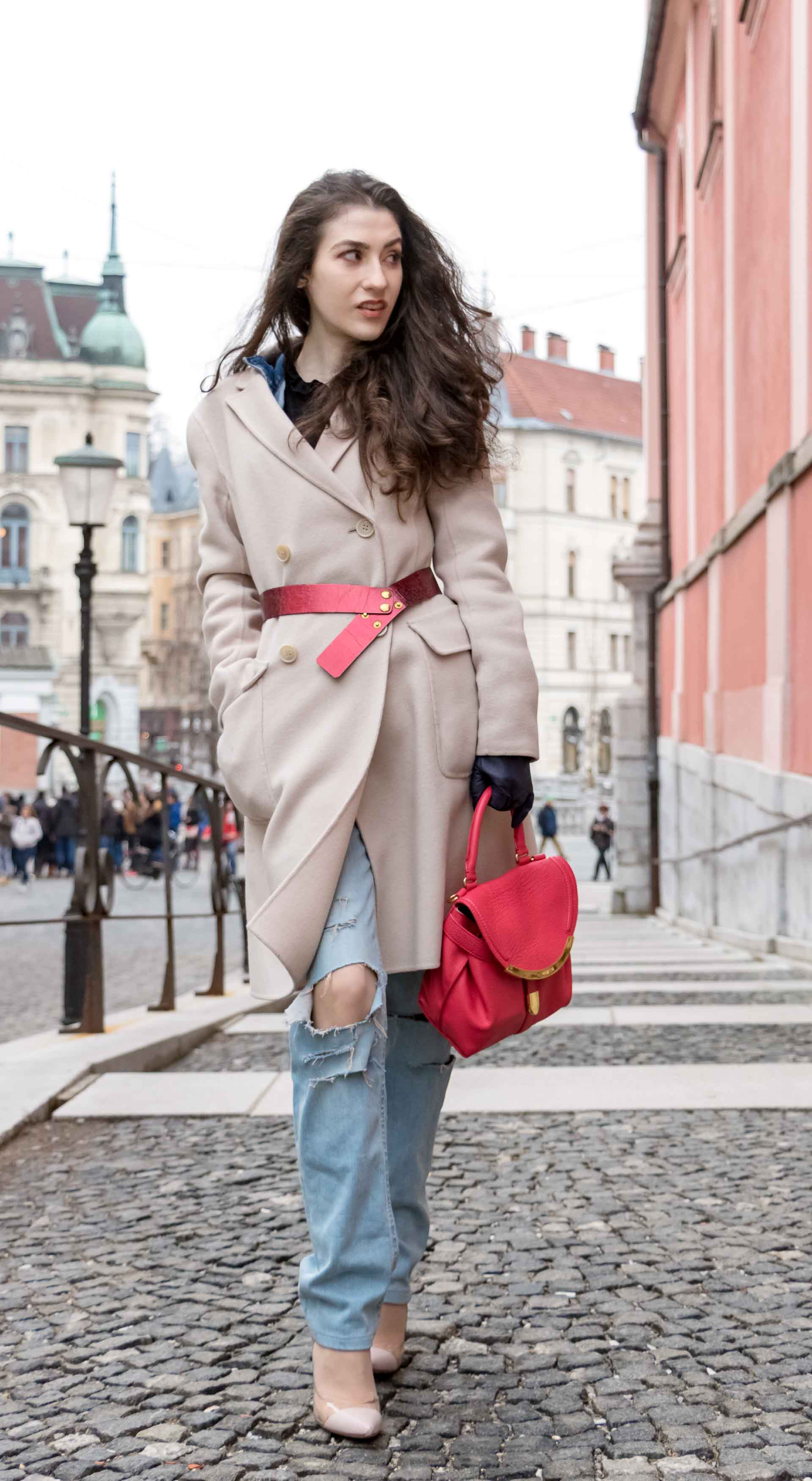 Fashion Blogger Veronika Lipar of Brunette from Wall Street wearing ripped blue Levi's jeans, off-white double breasted Weekend Maxmara coat, red dangling belt, blush Gianvito Rossi plexi pumps, See by Chloe pink top handle bag, blue leather gloves on the street of Ljubljana