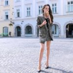 Fashion Blogger Veronika Lipar of Brunette from Wall Street dressed in Erika Cavallini oversized boyfriend plaid blazer with short tweed black and white mini skirt from streets, black pumps and white chain strap shoulder bag while eating ice cream
