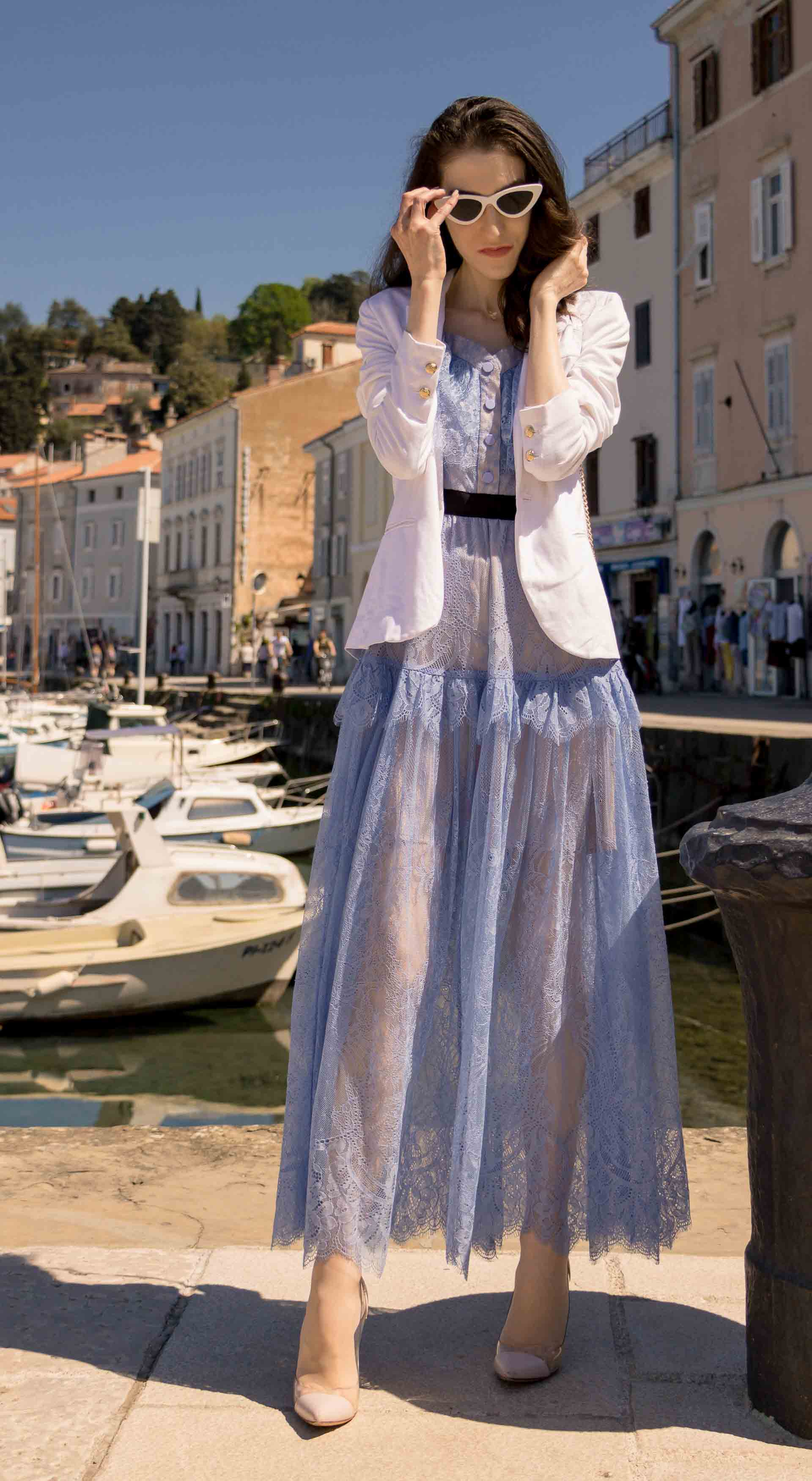 Veronika Lipar Fashion Blogger of Brunette from Wall Street dressed in Self-Portrait blue lace midi dress, white single button blazer, blush Gianvito Rossi plexi pumps, white shoulder bag, Lespecs white cat eye sunglasses while standing in the port in Piran