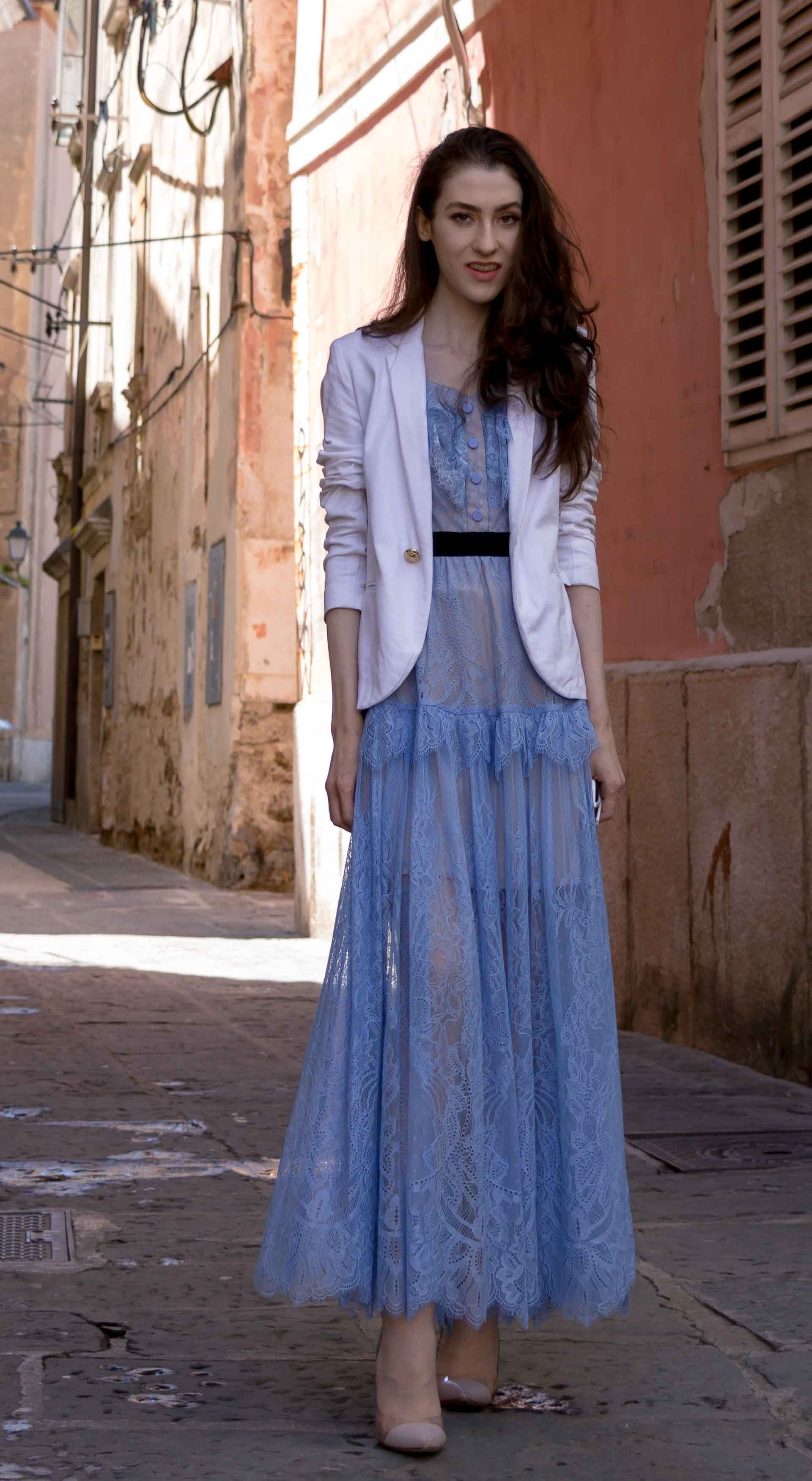Veronika Lipar Fashion Blogger of Brunette from Wall Street dressed in Self-Portrait blue lace midi dress, white single button blazer, blush Gianvito Rossi plexi pumps, white shoulder bag, Lespecs white cat eye sunglasses while standing hidden alley in Italian town