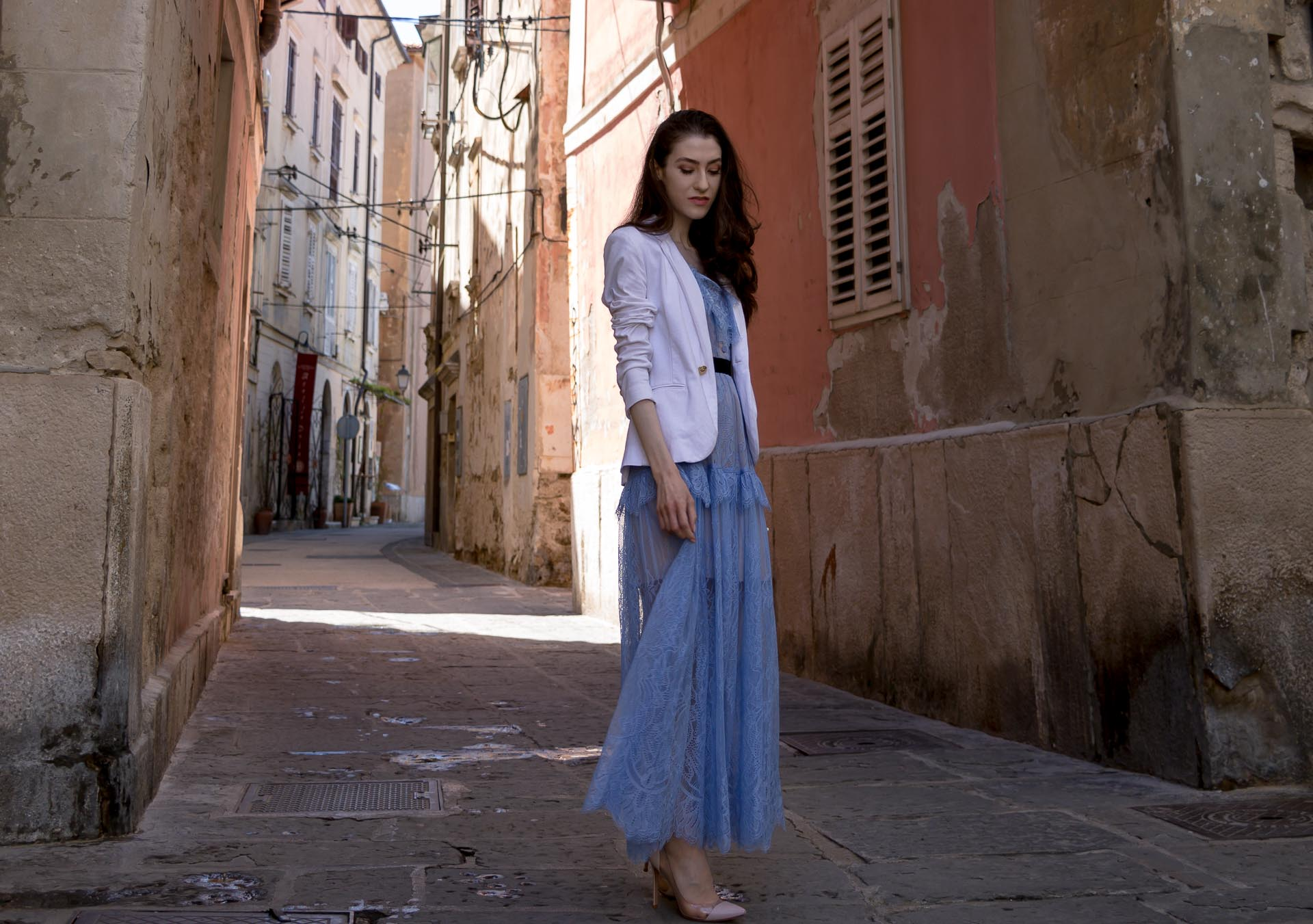 Veronika Lipar Fashion Blogger of Brunette from Wall Street dressed in Self-Portrait blue lace midi dress, white single button blazer, blush Gianvito Rossi plexi pumps, white shoulder bag, Lespecs white cat eye sunglasses while standing hidden alley in small Italian village