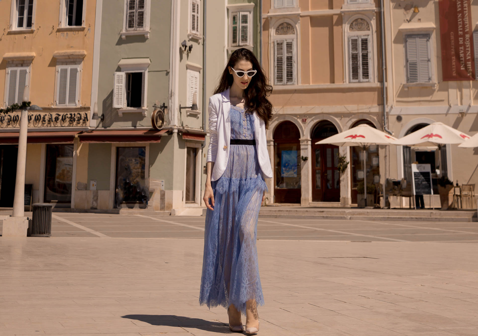 Veronika Lipar Fashion Blogger of Brunette from Wall Street dressed in Self-Portrait blue lace dress, white single button blazer, blush Gianvito Rossi plexi pumps, white shoulder bag, Lespecs white cat eye sunglasses while walking in the port in Piran
