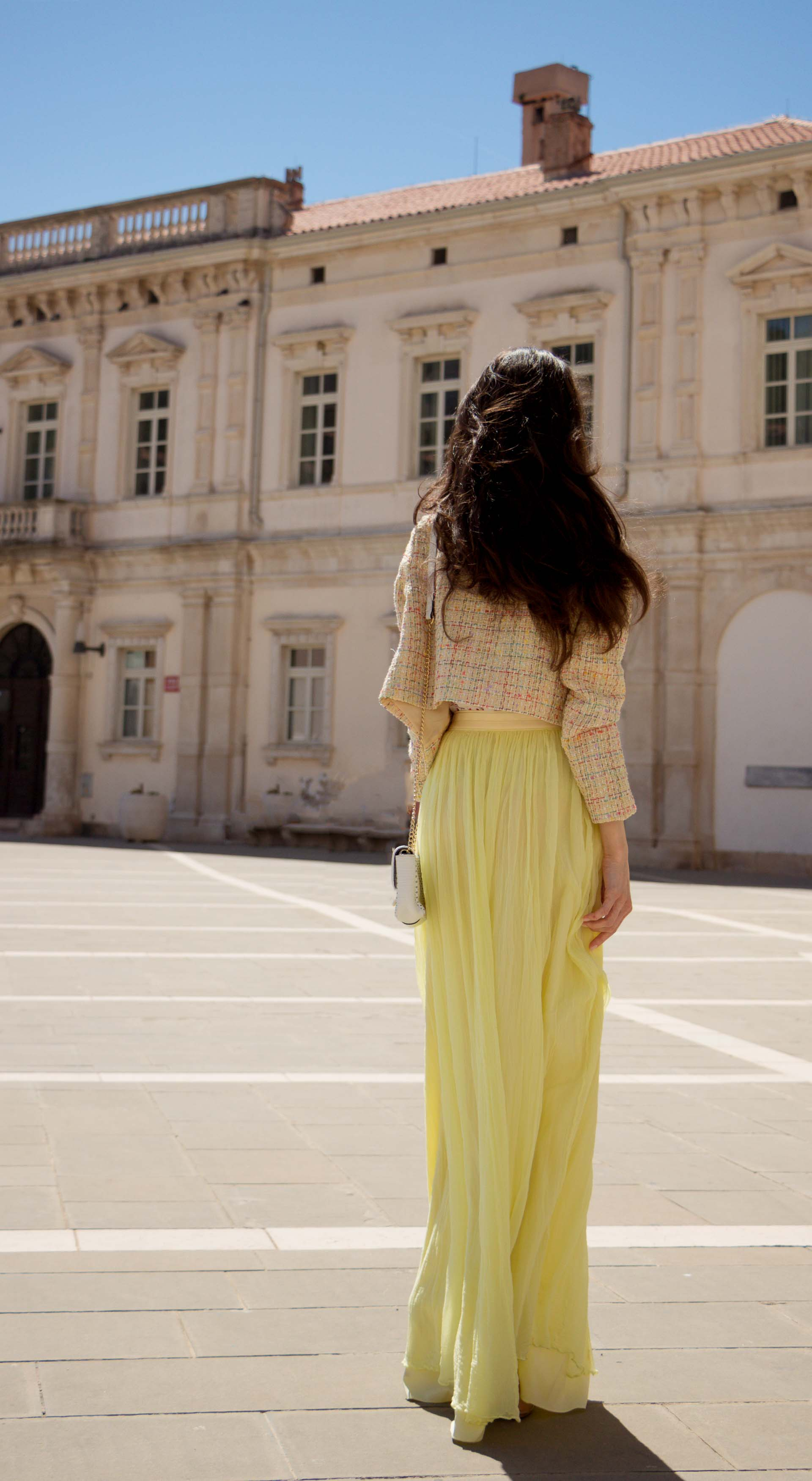 Veronika Lipar Fashion Blogger of Brunette from Wall Street wearing maxi yellow tulle skirt from Needle & Thread, short yellow tweed jacket from Storets, floral silk top, blush Gianvito Rossi plexi pumps, white shoulder bag while walking at the square in Venice