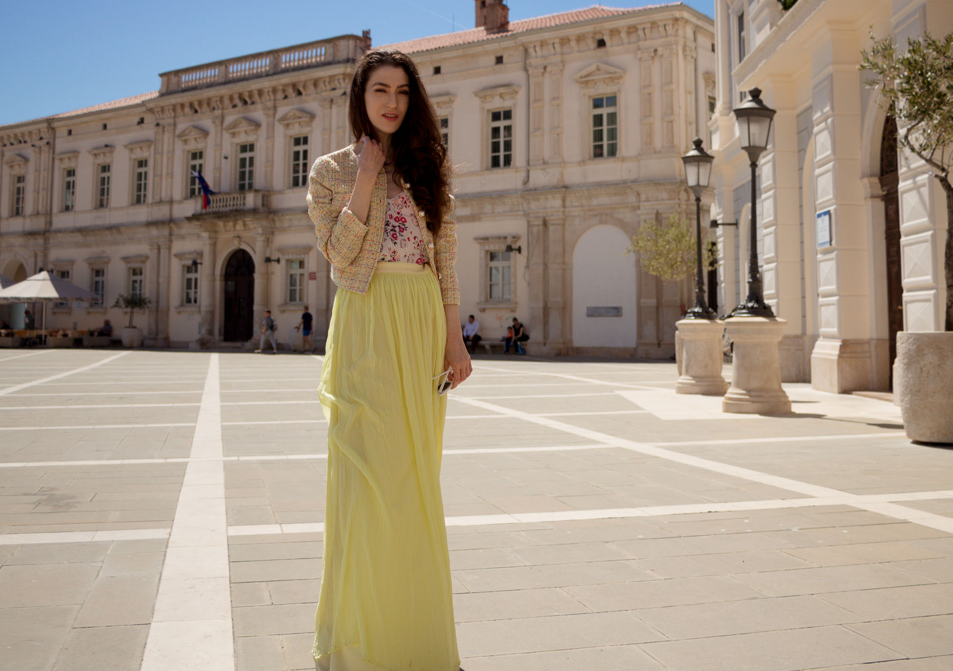Veronika Lipar Fashion Blogger of Brunette from Wall Street wearing long yellow tulle skirt from Needle & Thread, short yellow tweed jacket from Storets, floral silk top, blush Gianvito Rossi plexi pumps, white shoulder bag, Le specs white cat eye sunglasses walking at the square in Venice