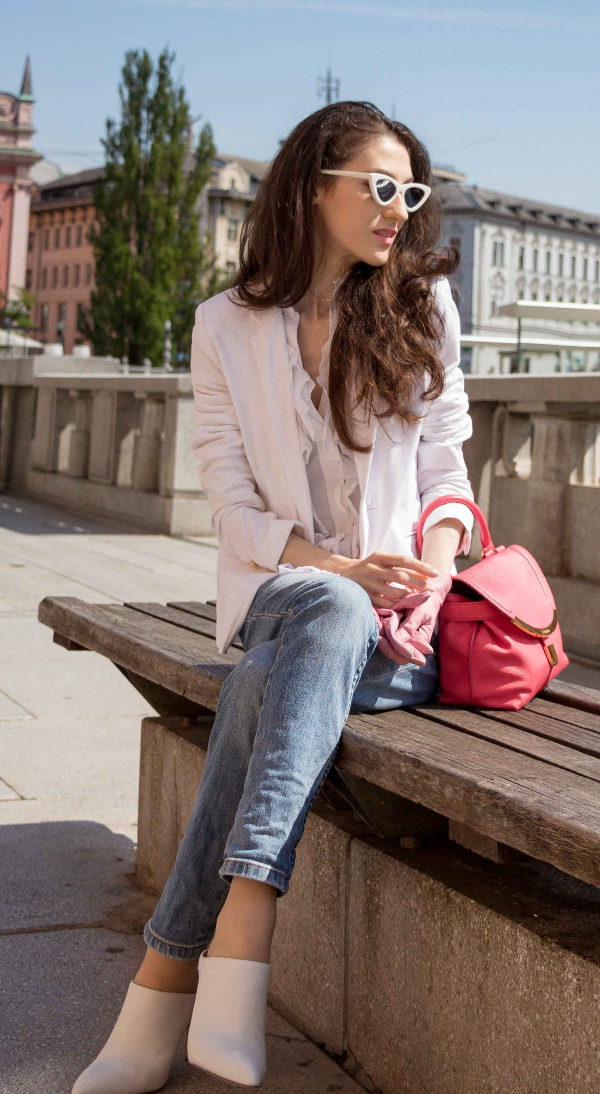 Veronika Lipar Fashion Blogger of Brunette from Wall Street wearing white mules, blue A.P.C. mom jeans, white fringe blouse, white blazer, pink gloves, pink top handle bag and Le Specs Lolita white cat eye sunglasses while sitting on the bench