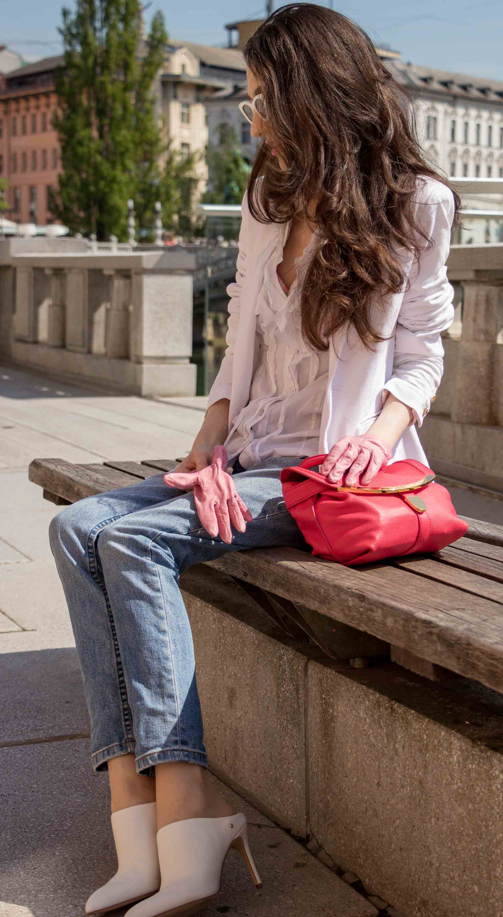 Veronika Lipar Fashion Blogger of Brunette from Wall Street wearing white mules, blue A.P.C. mom jeans, white fringe blouse, white blazer, pink gloves, pink top handle bag and Le Specs Lolita white cat eye sunglasses while sitting on the bench in Ljubljana