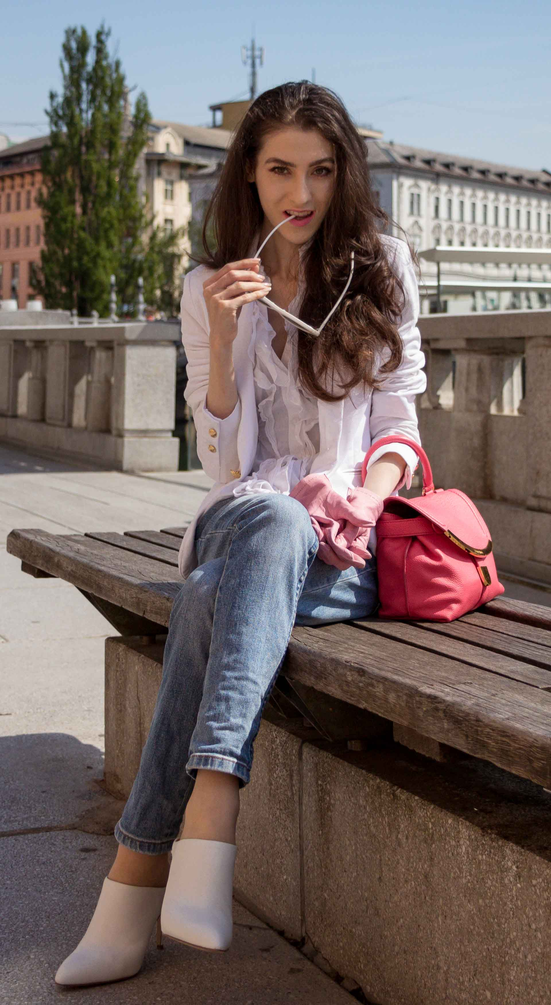 Veronika Lipar Fashion Blogger of Brunette from Wall Street dressed in white mules, blue A.P.C. mom jeans, white fringe blouse, white blazer, pink gloves, pink top handle bag and Le Specs Lolita white cat eye sunglasses while sitting on the bench
